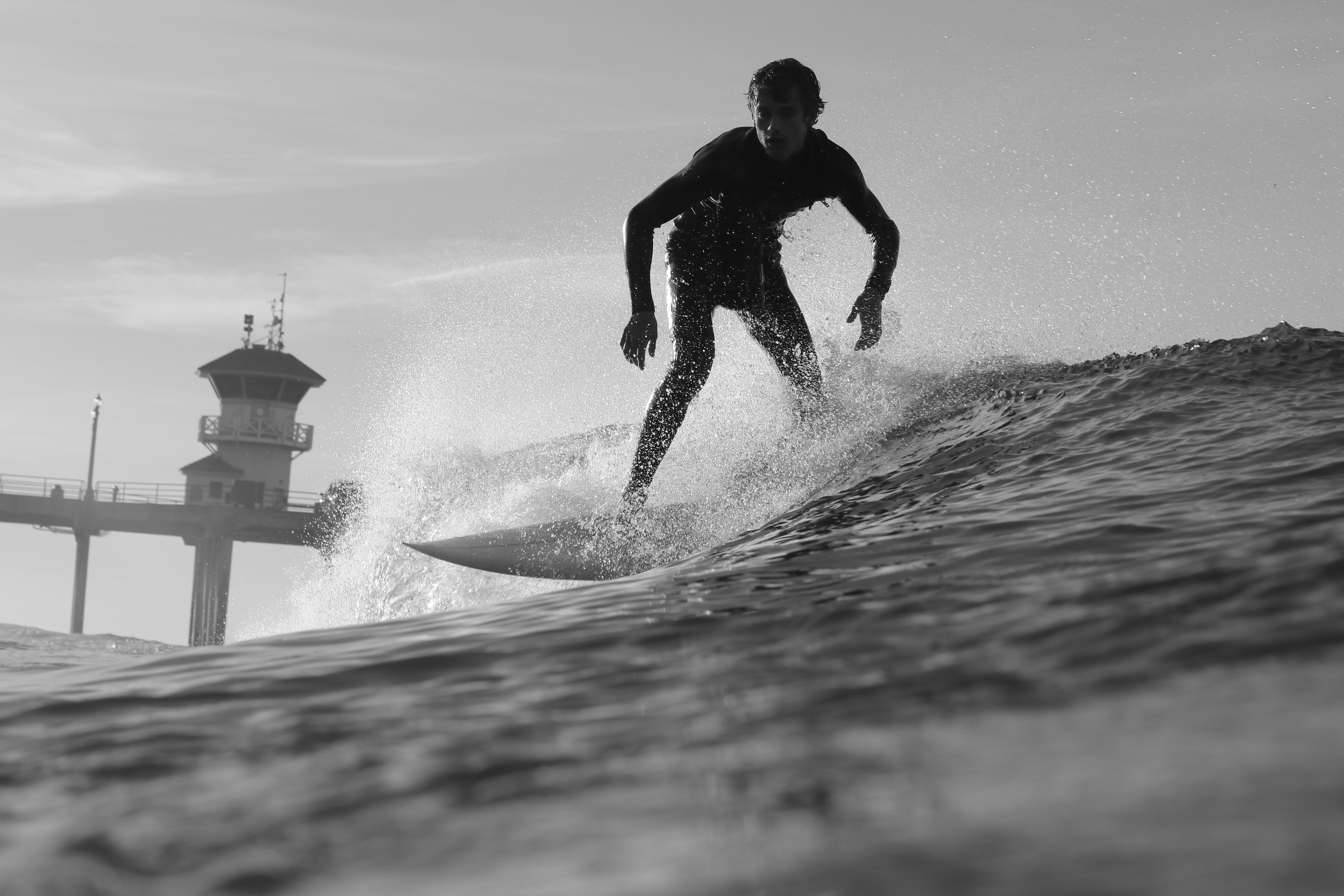 A surfer wearing a wetsuit, catching a wave in Huntington Beach right by the pier