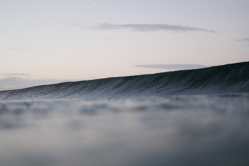 time lapsed photography of ocean wave under clear sky