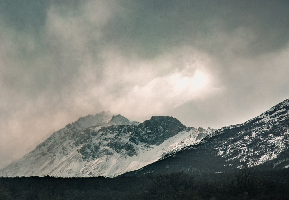 snow covered mountaan under gray sky