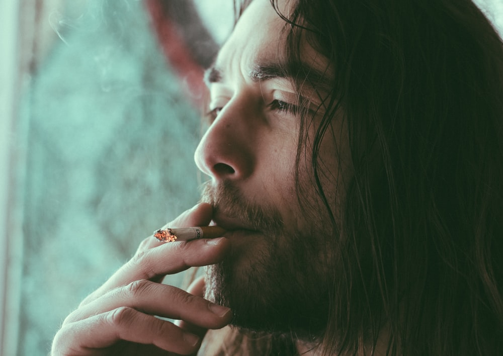 man smoking red cigarette