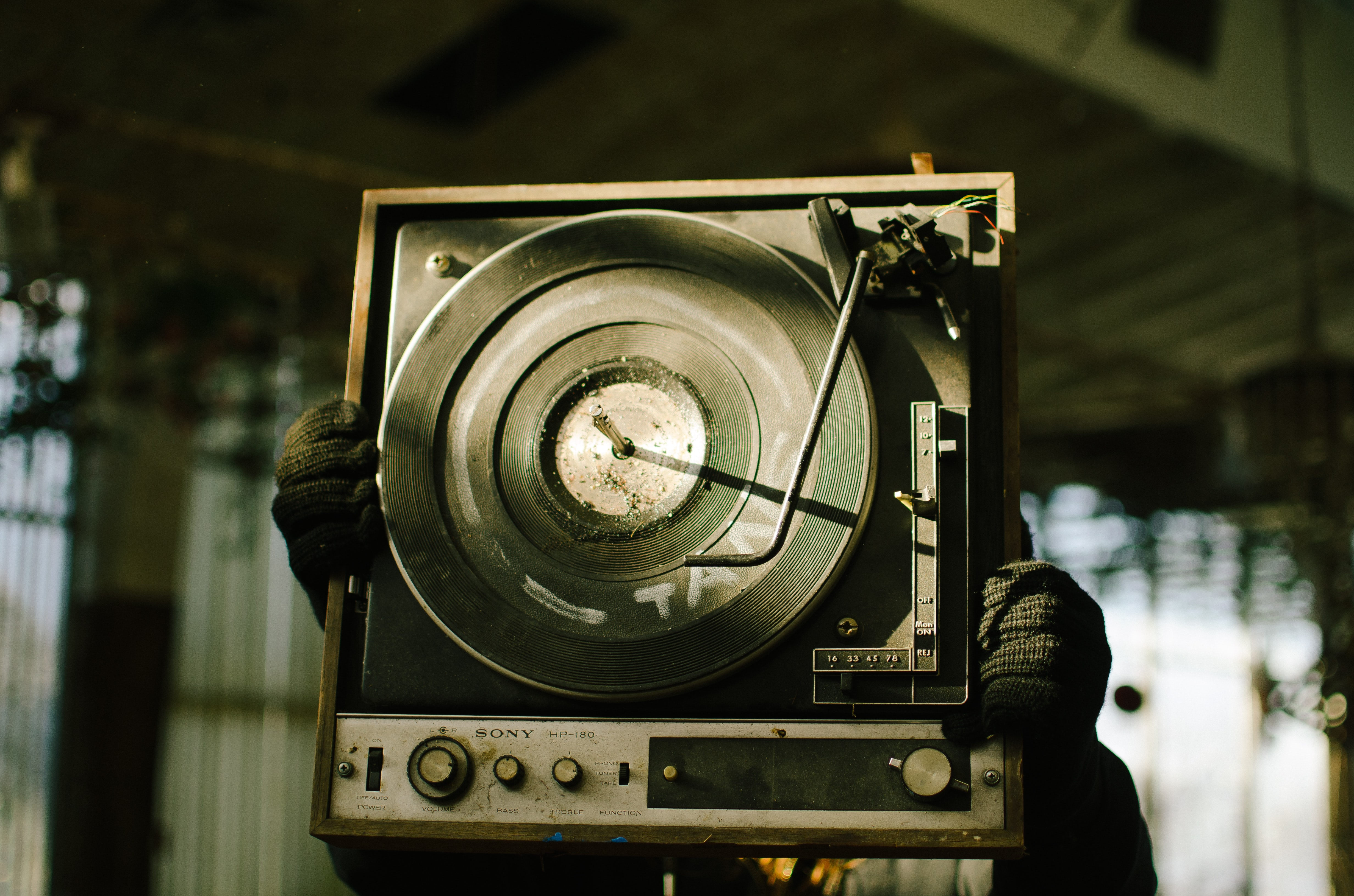 A person holding up a decrepit Sony record player