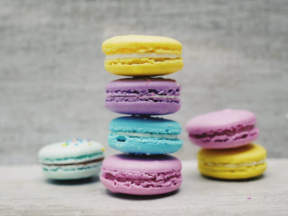 four macarons balancing near two and one macarons