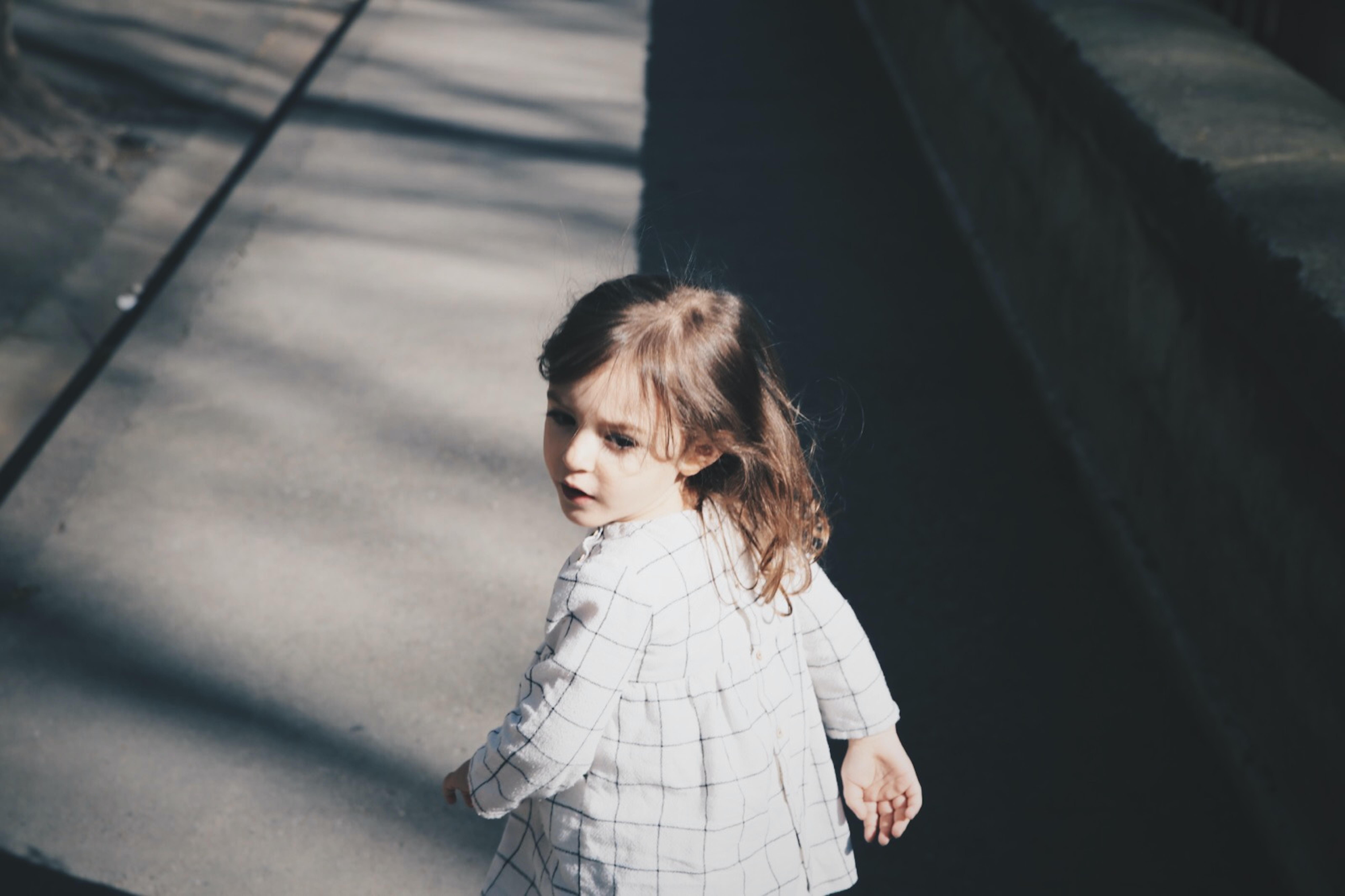 toddler girl walking on gray concrete road at daytime