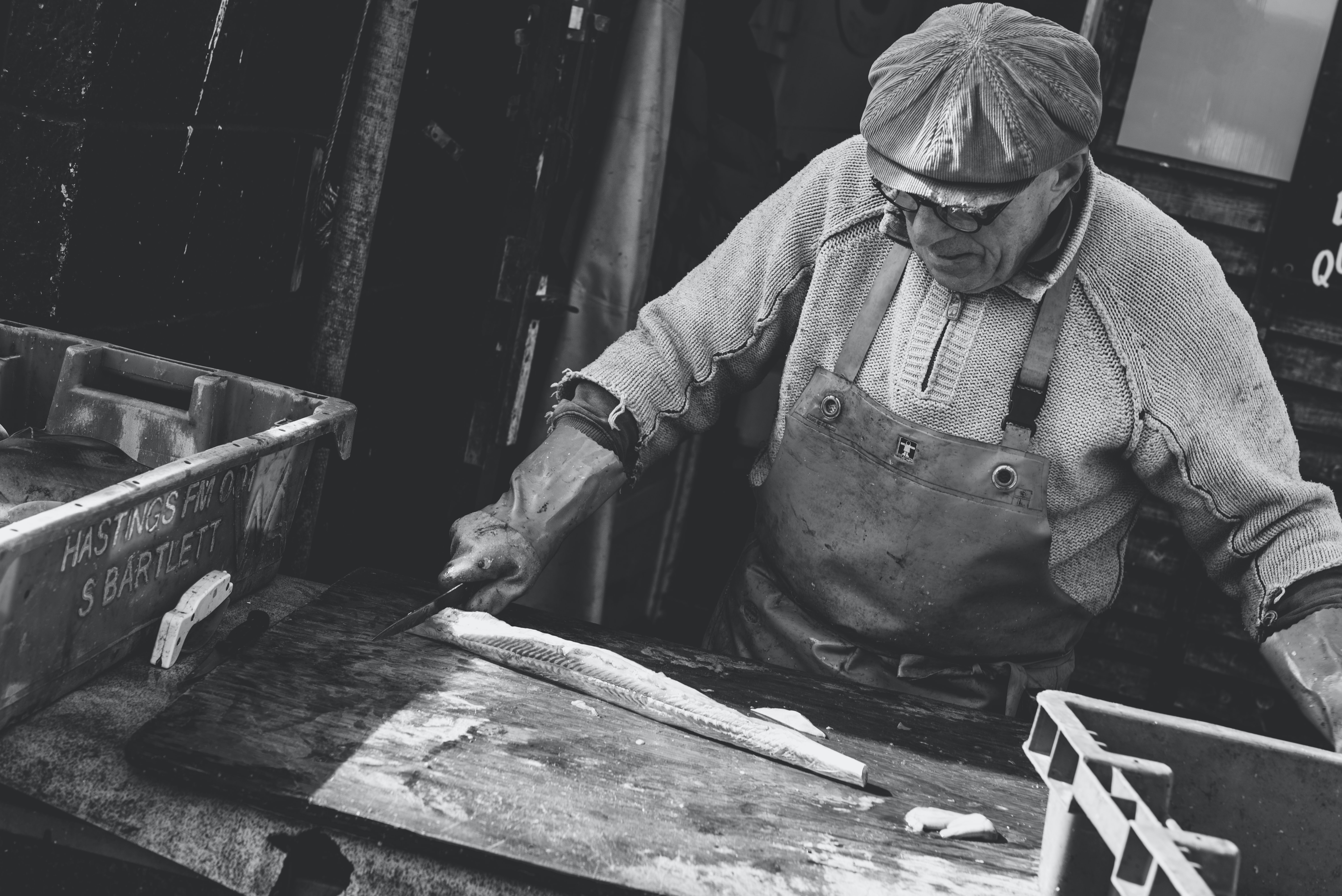 An old fisherman wearing an apron and a cap cutting a fish on a cutting board.