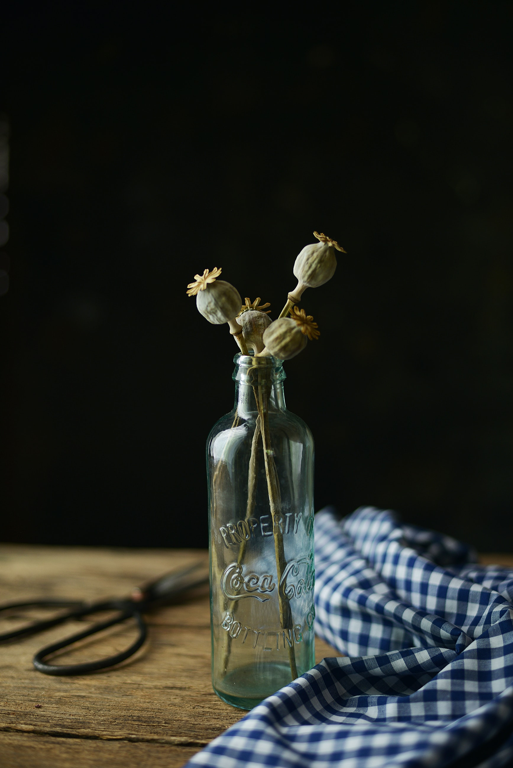 clear glass bottle with white flowers on table