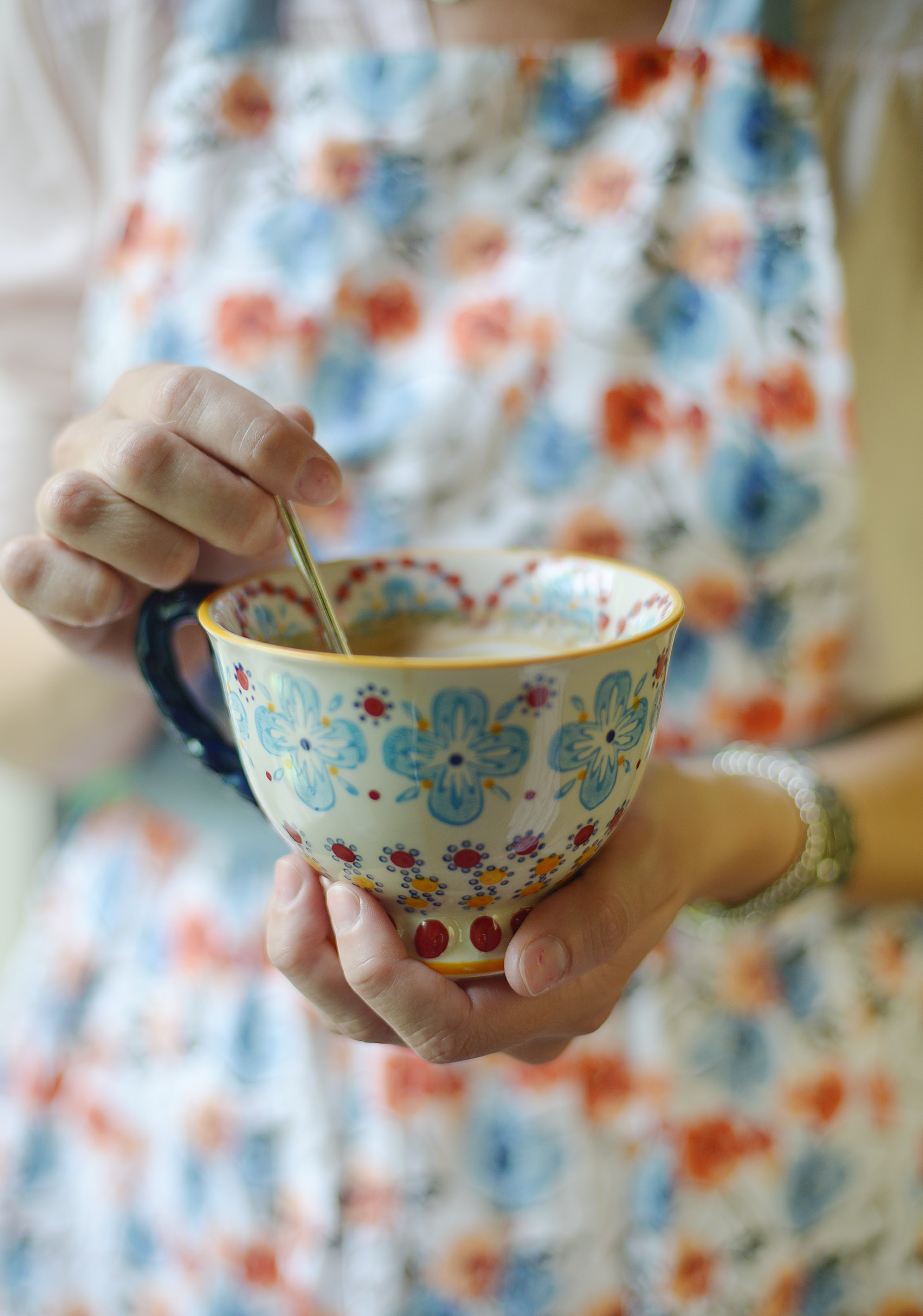 A woman in a floral dress stirring tea in a floral teacup