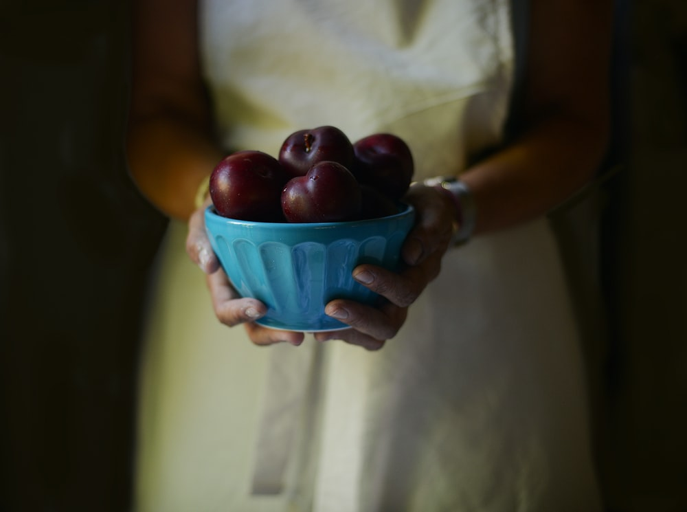 woman holding bowl filled with apples