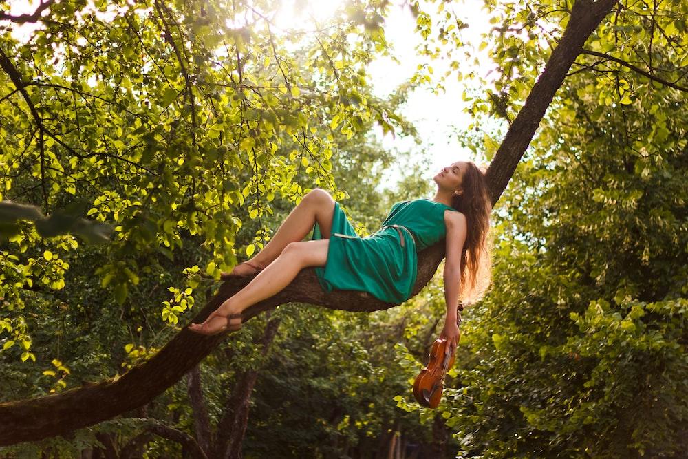 woman in green dress lying on tree branch