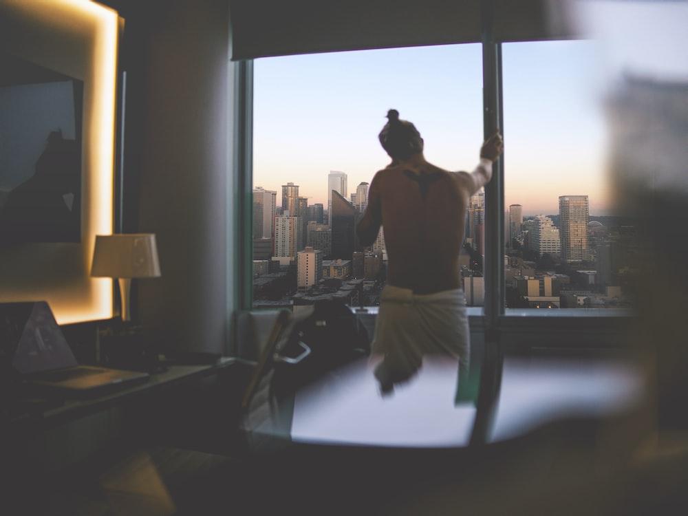 man standing beside window during daytime