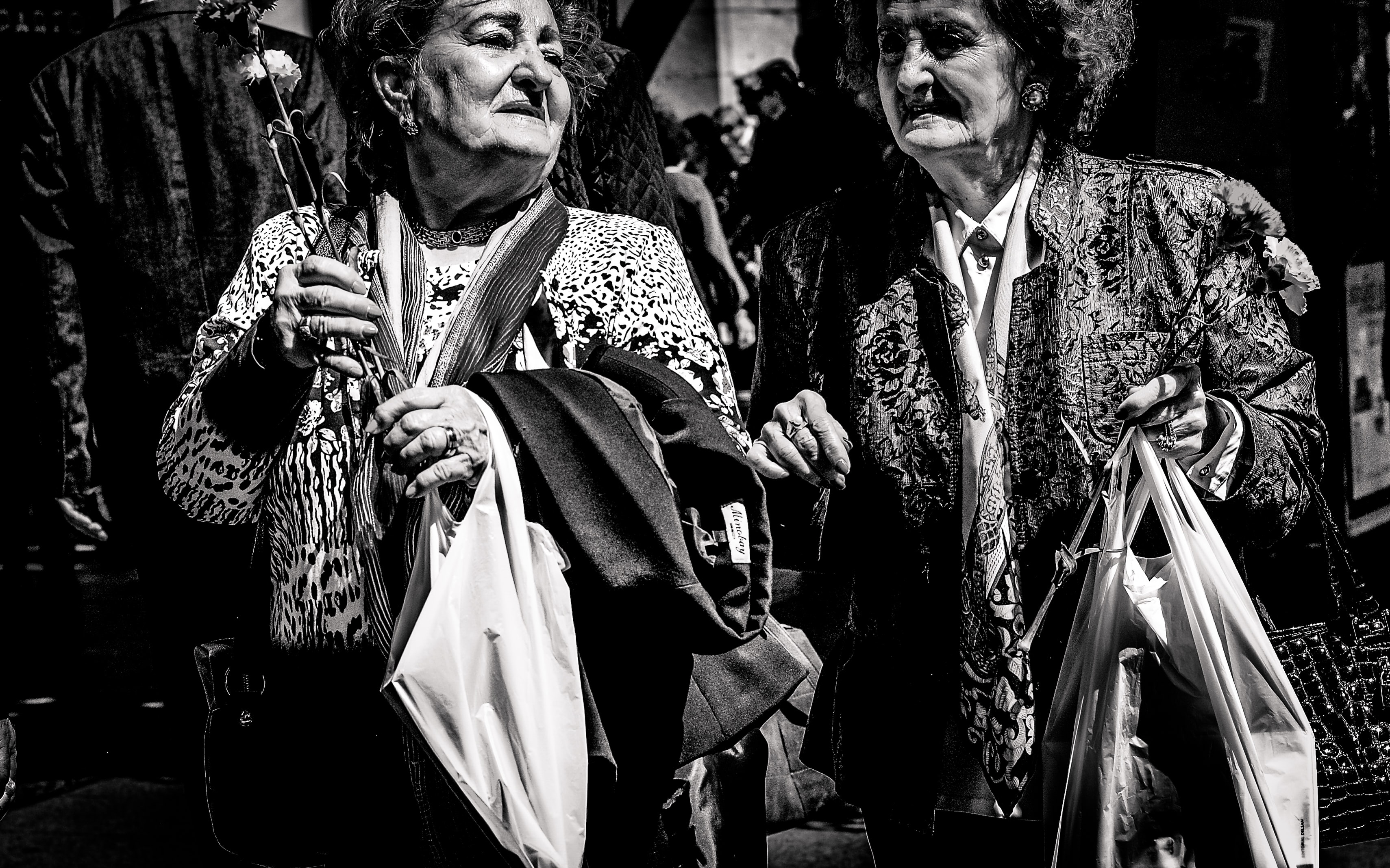 Black and white shot of two old women carrying bags in Zaragoza