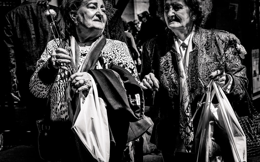grayscale photo of two women holding bags