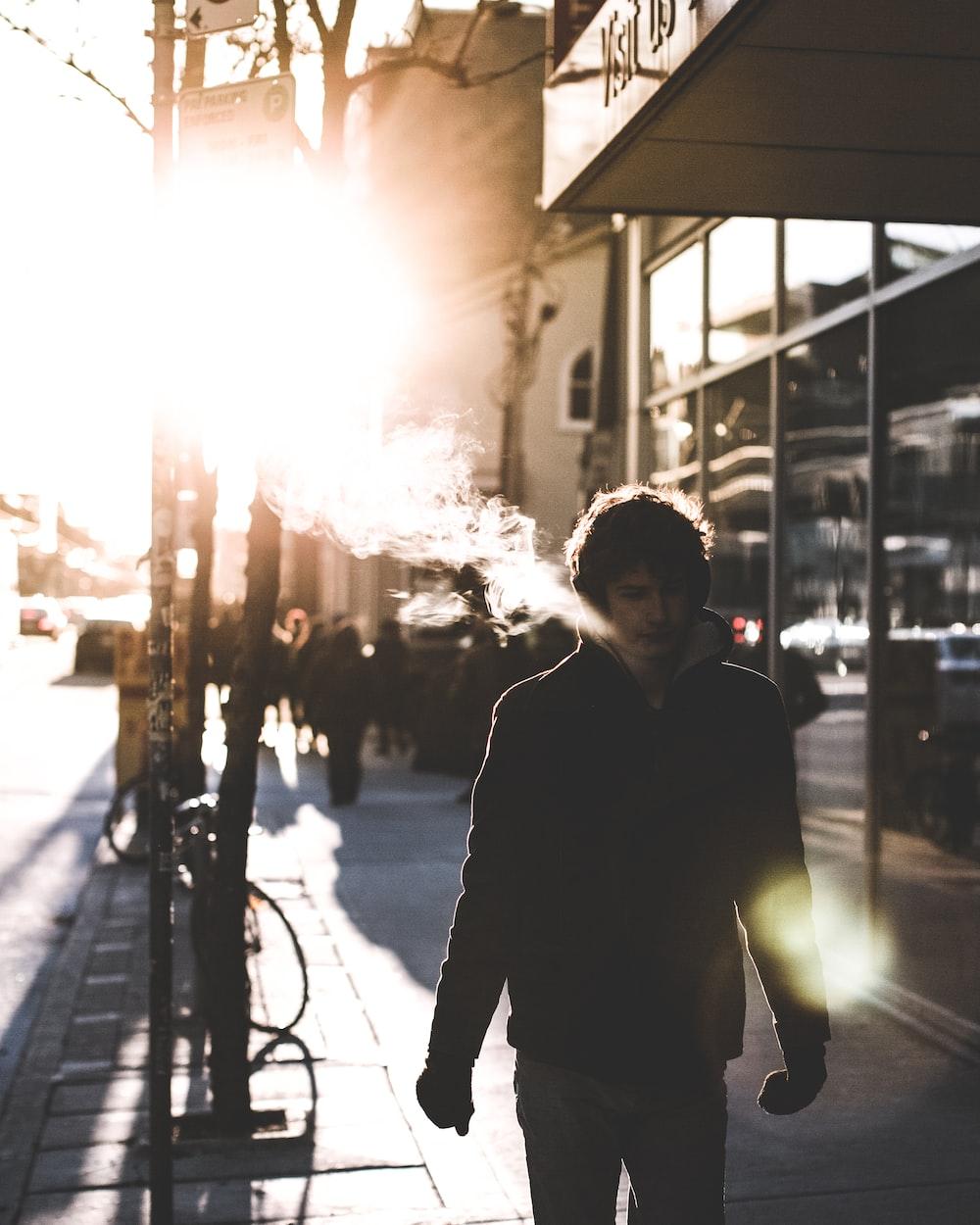 man walking on sidewalk beside glass wall