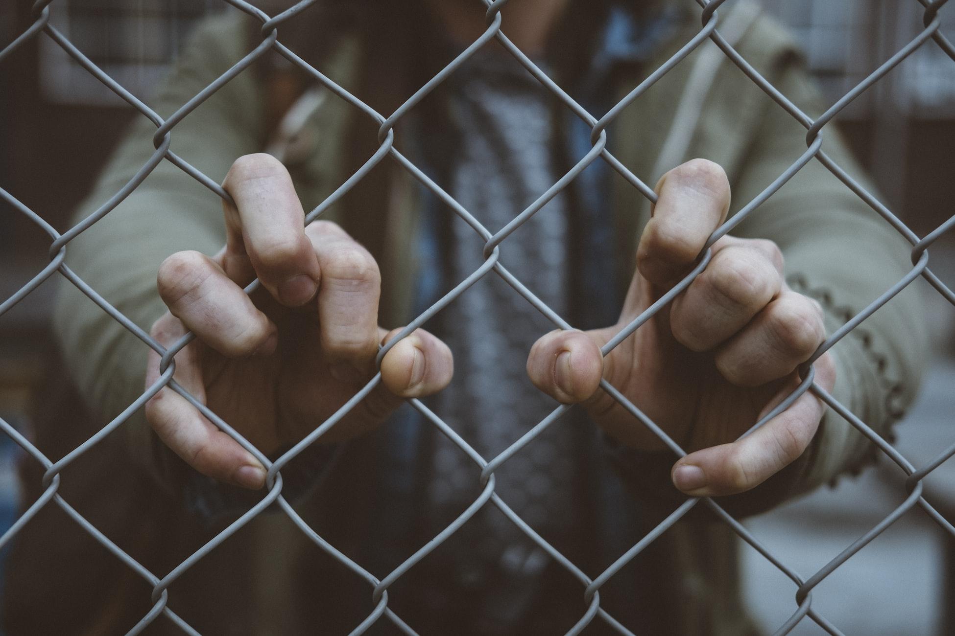 Člověk držící se drátěného plotu, zřejmě uvězněný. Podobný pocit jako autistický shutdown.