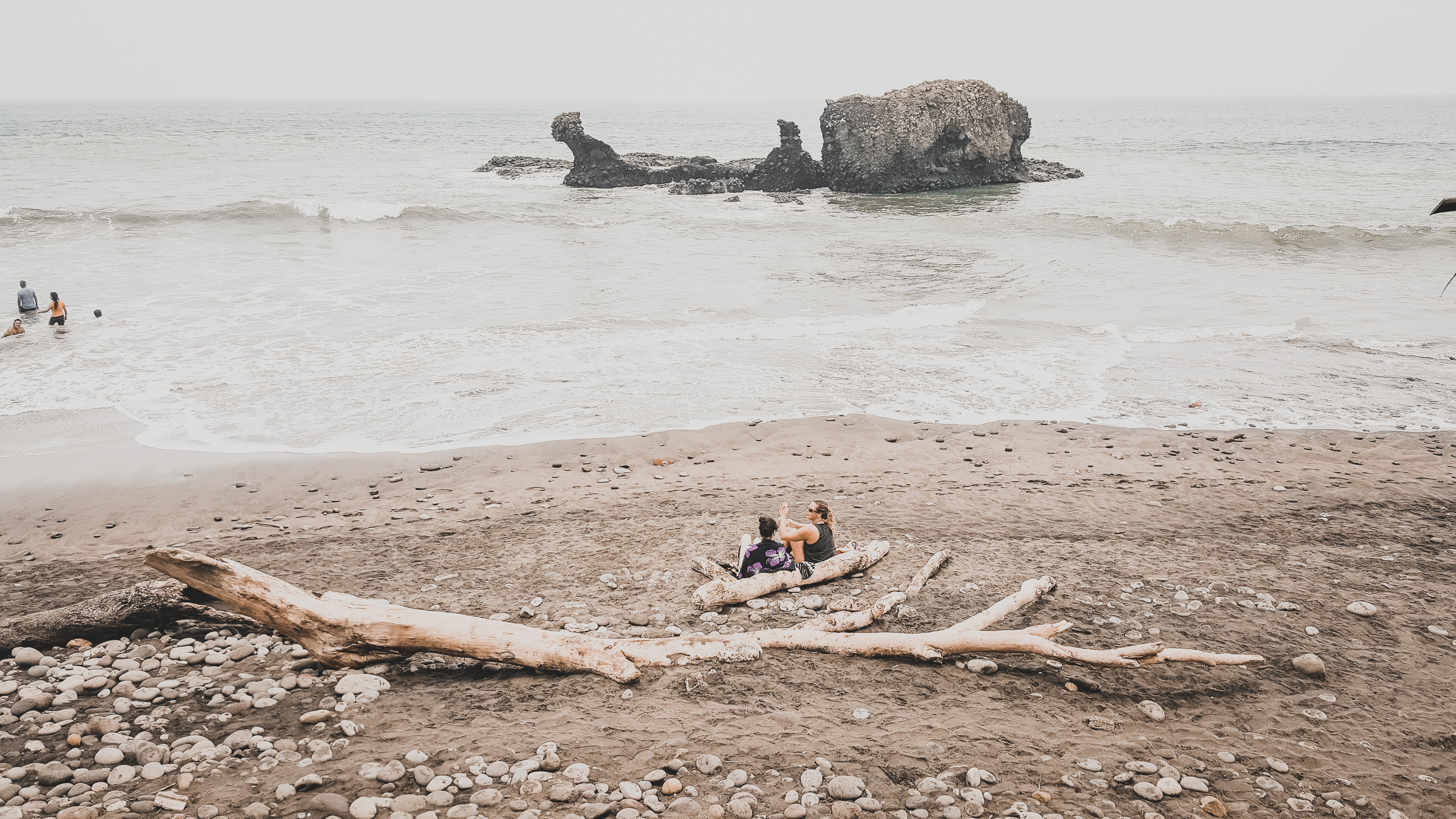 People hanging out on a beach sitting on driftwood and swimming in the ocean