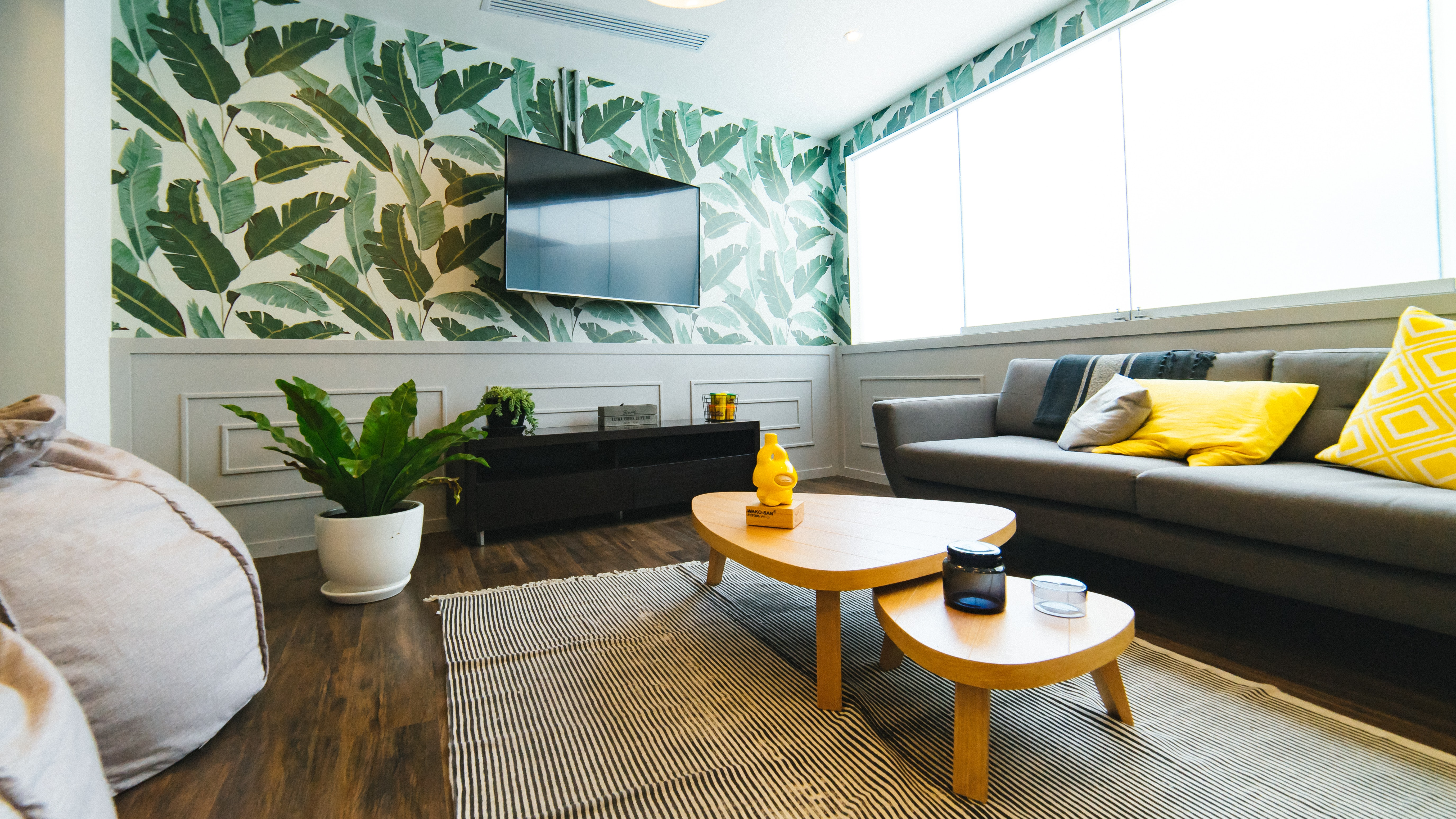 A room with palm print wallpaper, bean bag chairs, a couch, coffee table, rug, and tv at Communal Coworking