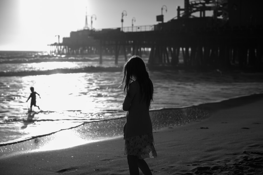 grayscale photography of woman standing in beach