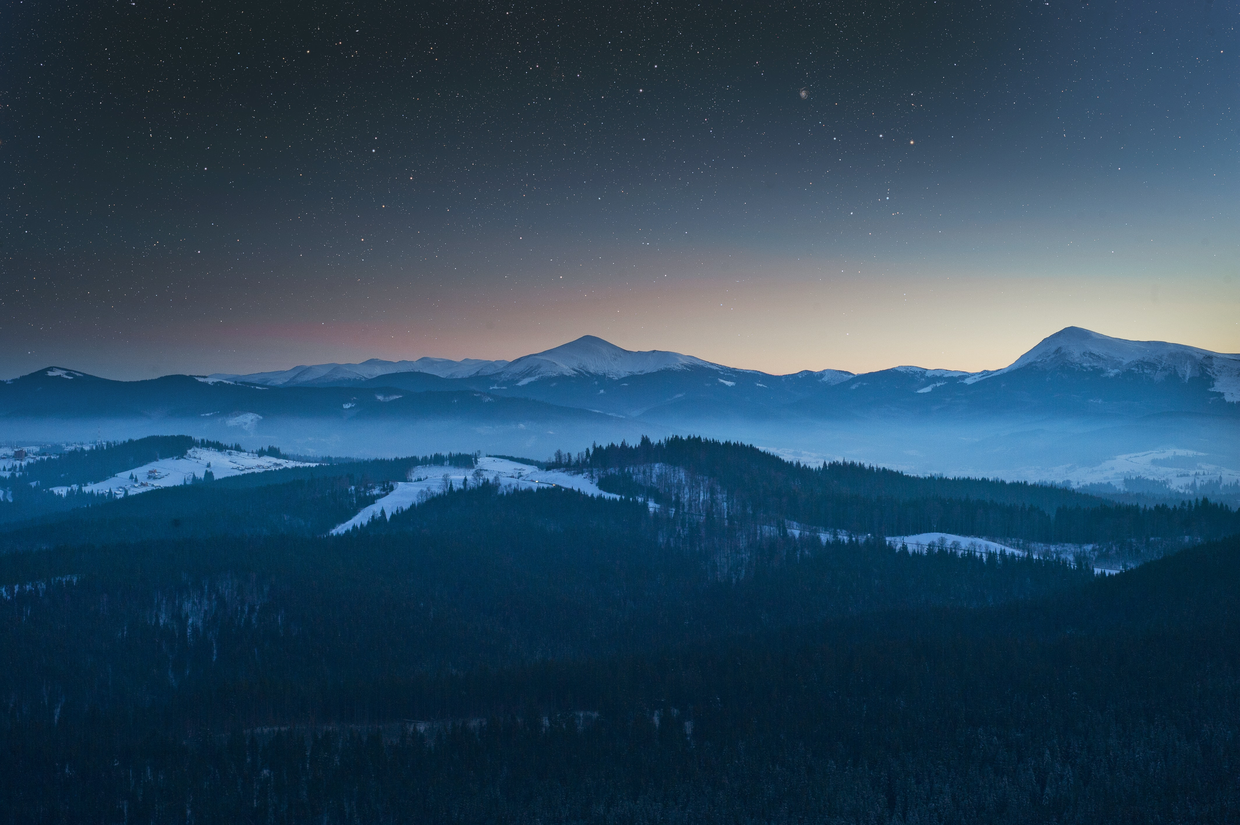 View of a starry night at Bukovel with forests and mountain ranges shrouded in the dusk