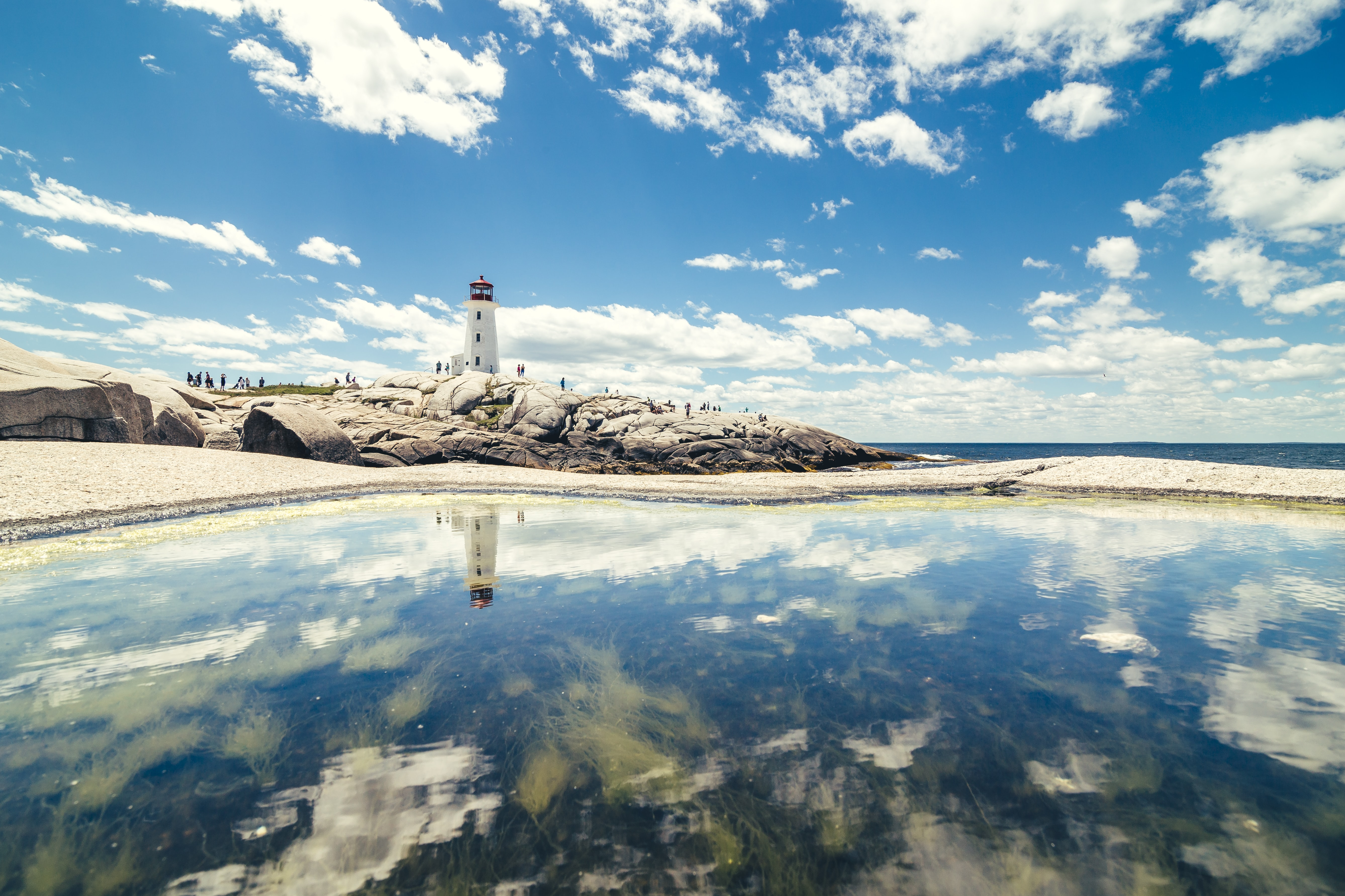 lighthouse tower near calm water under white clouds and blue sky