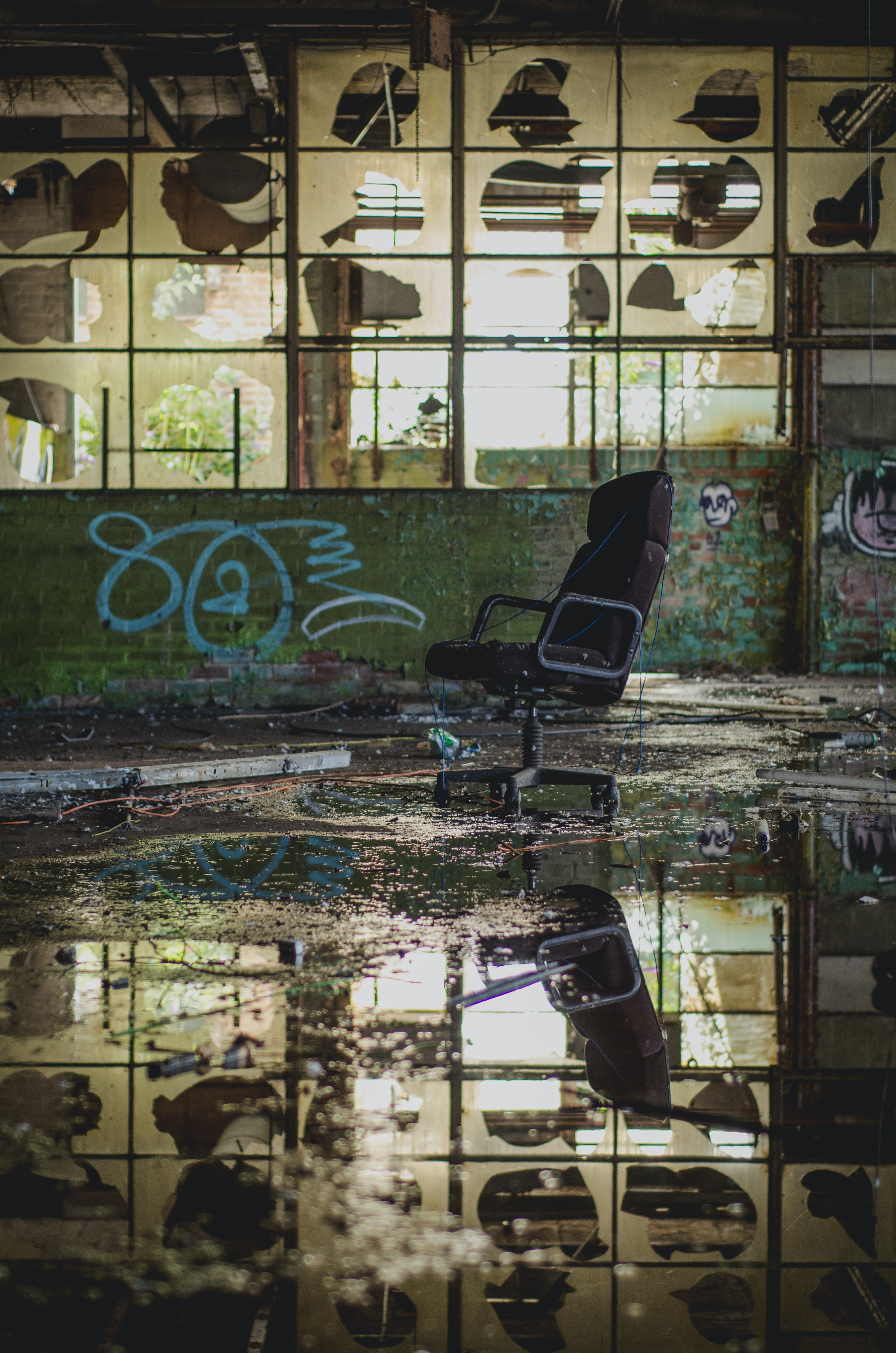 Abandoned urban warehouse with chair and water reflection with graffiti tags on wall, Sheffield United Kingdom
