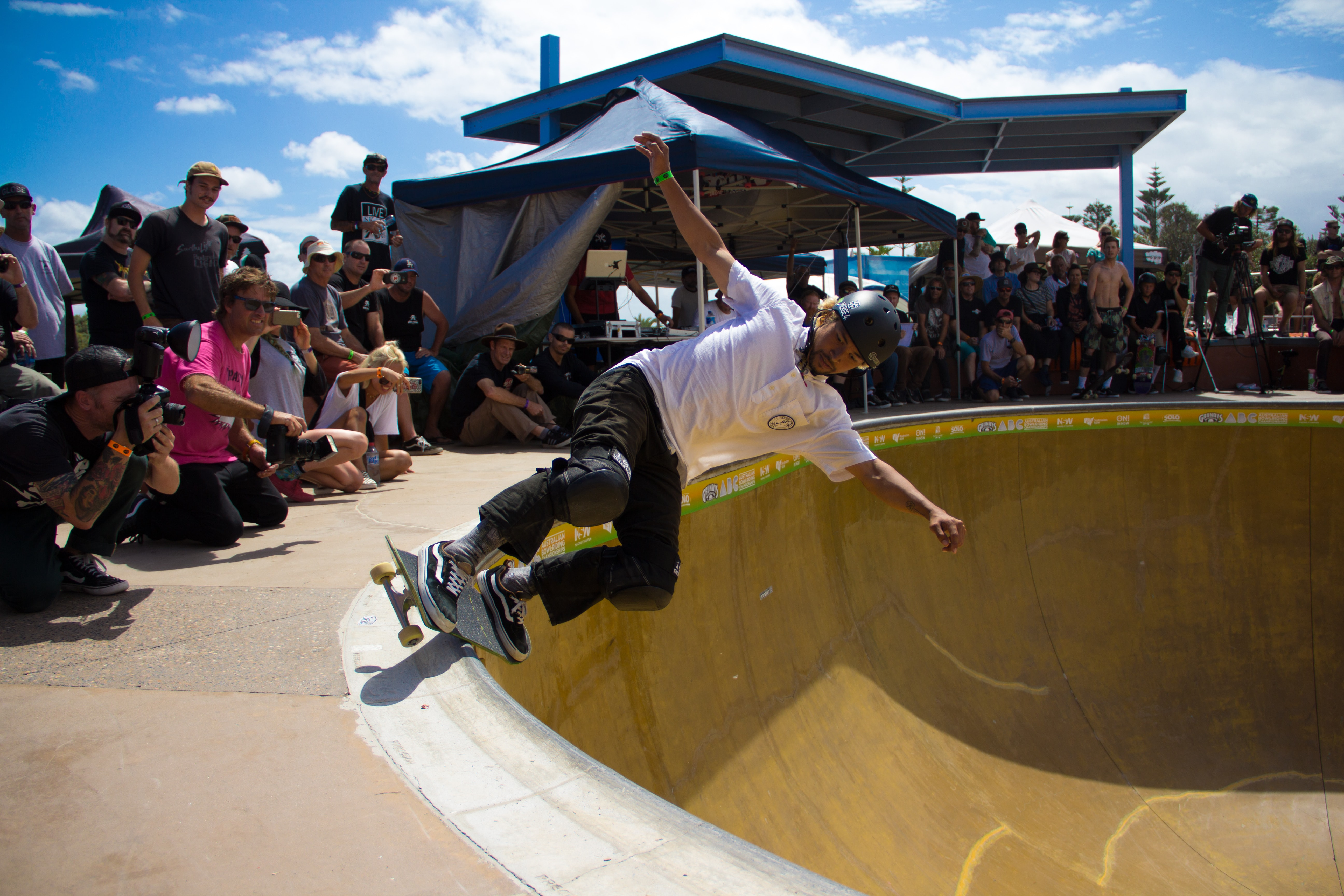 A diverse crowd cheers on a skateboarder in a skate park competition