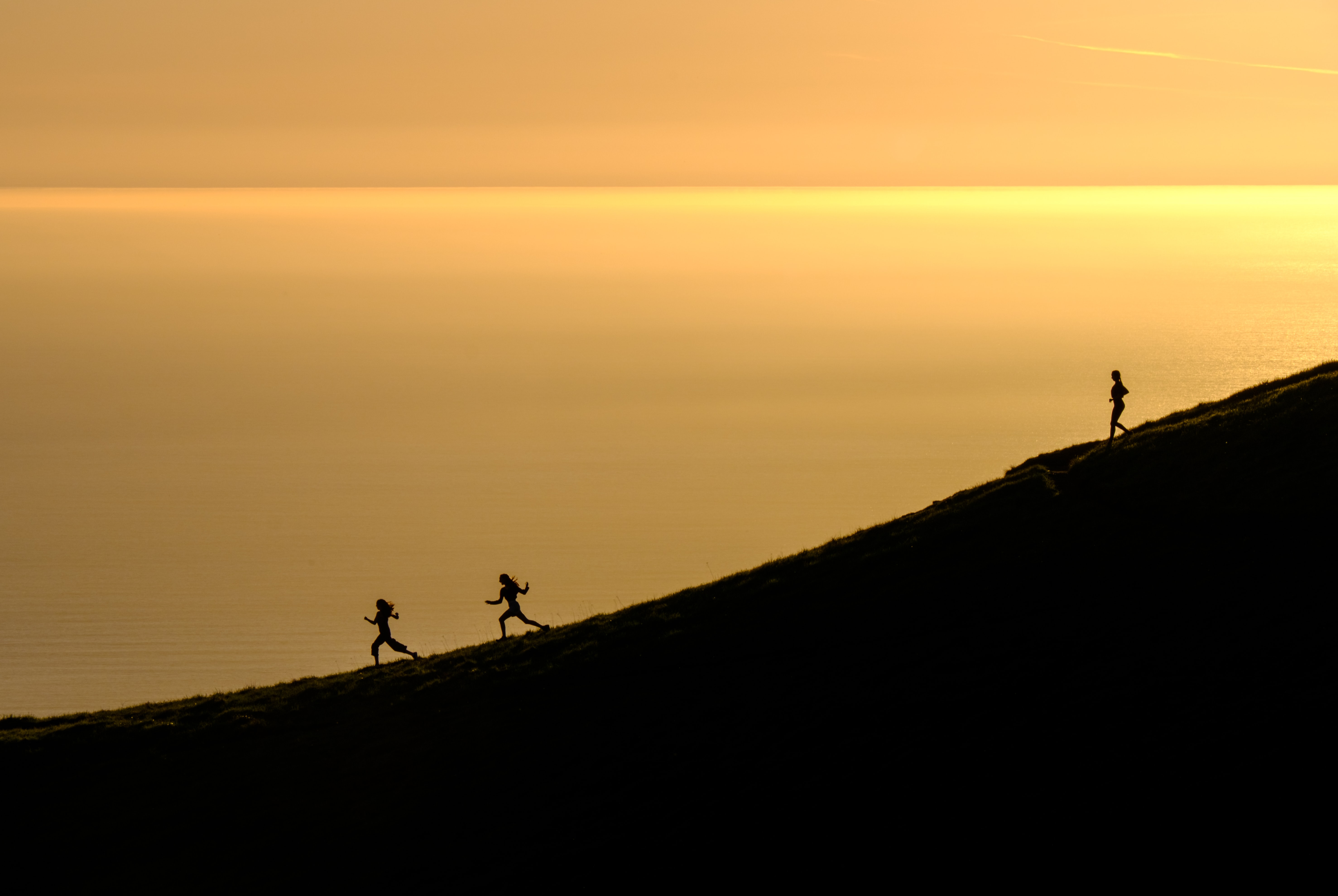 Three women energetically running down Mount Tamalpais as waters in the distance reflect the golden sunset