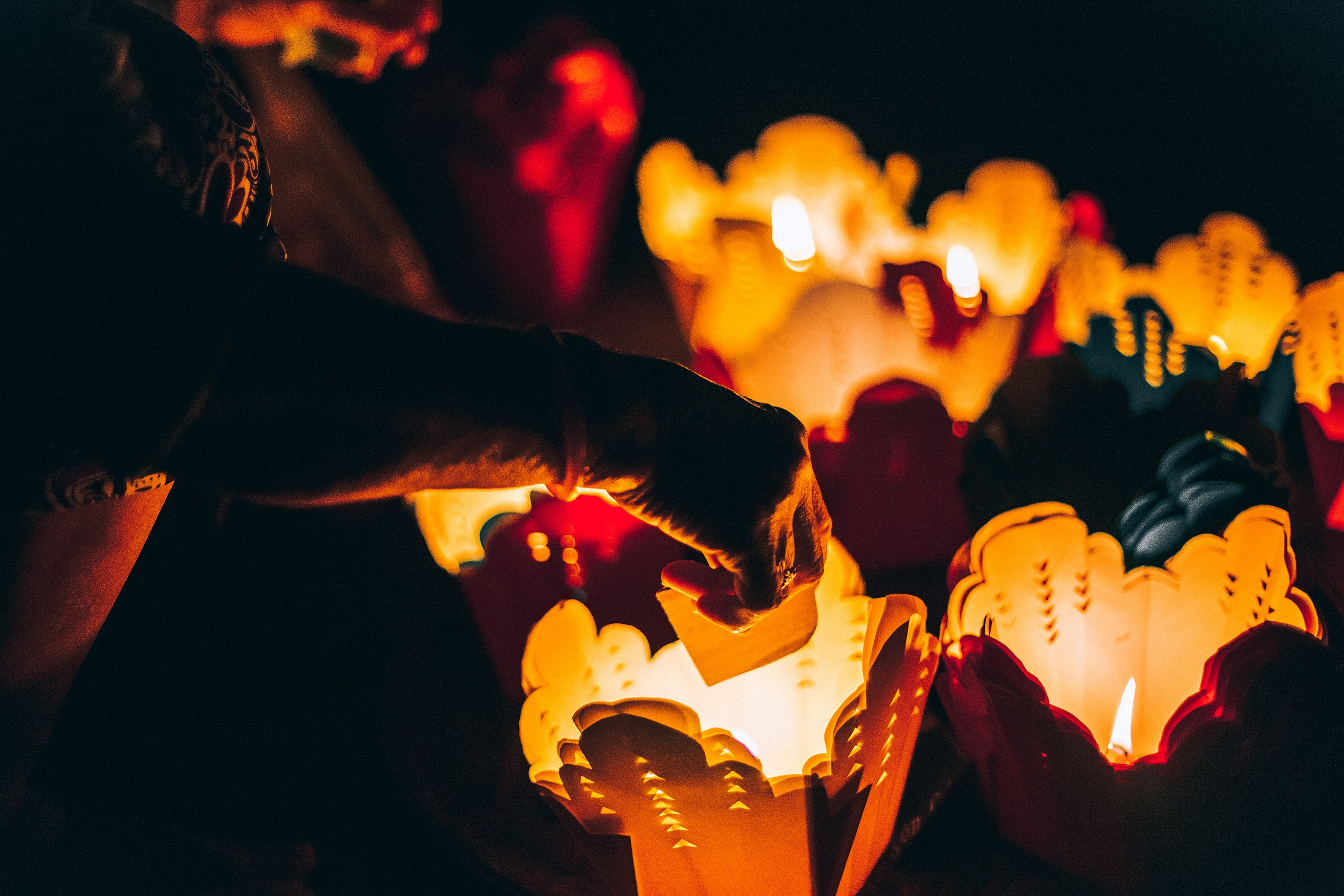 Person places candles inside paper takeout container lanterns
