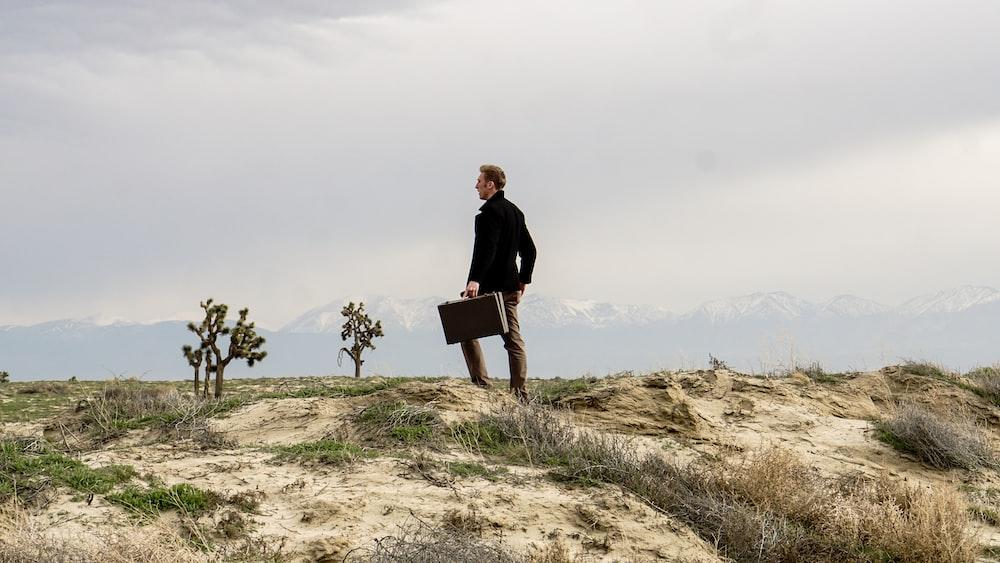 昼間に茶色の野原に立っている人