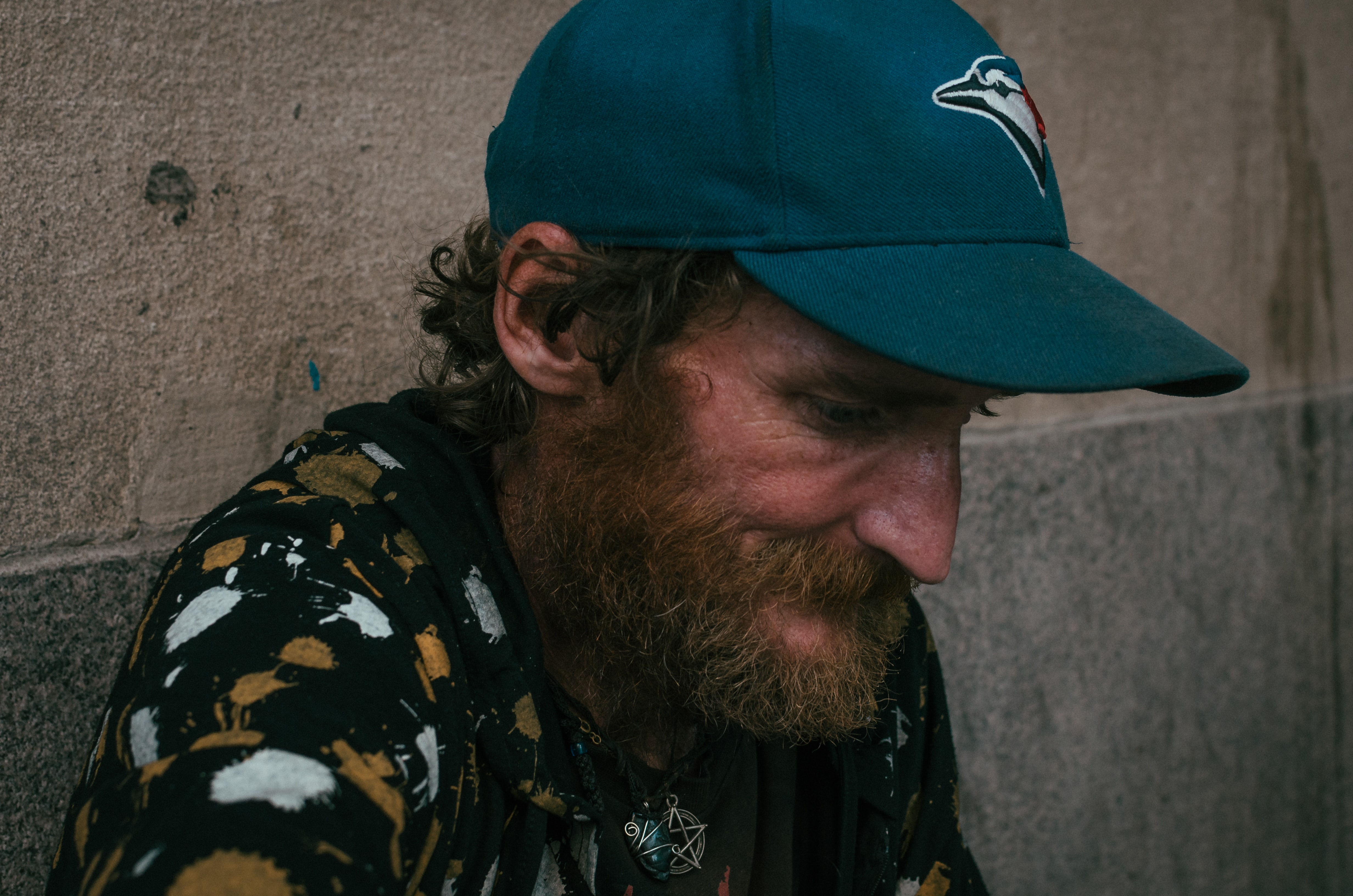 A bearded man wearing a Blue Jays cap and a pentagram pendant looks down while sitting.