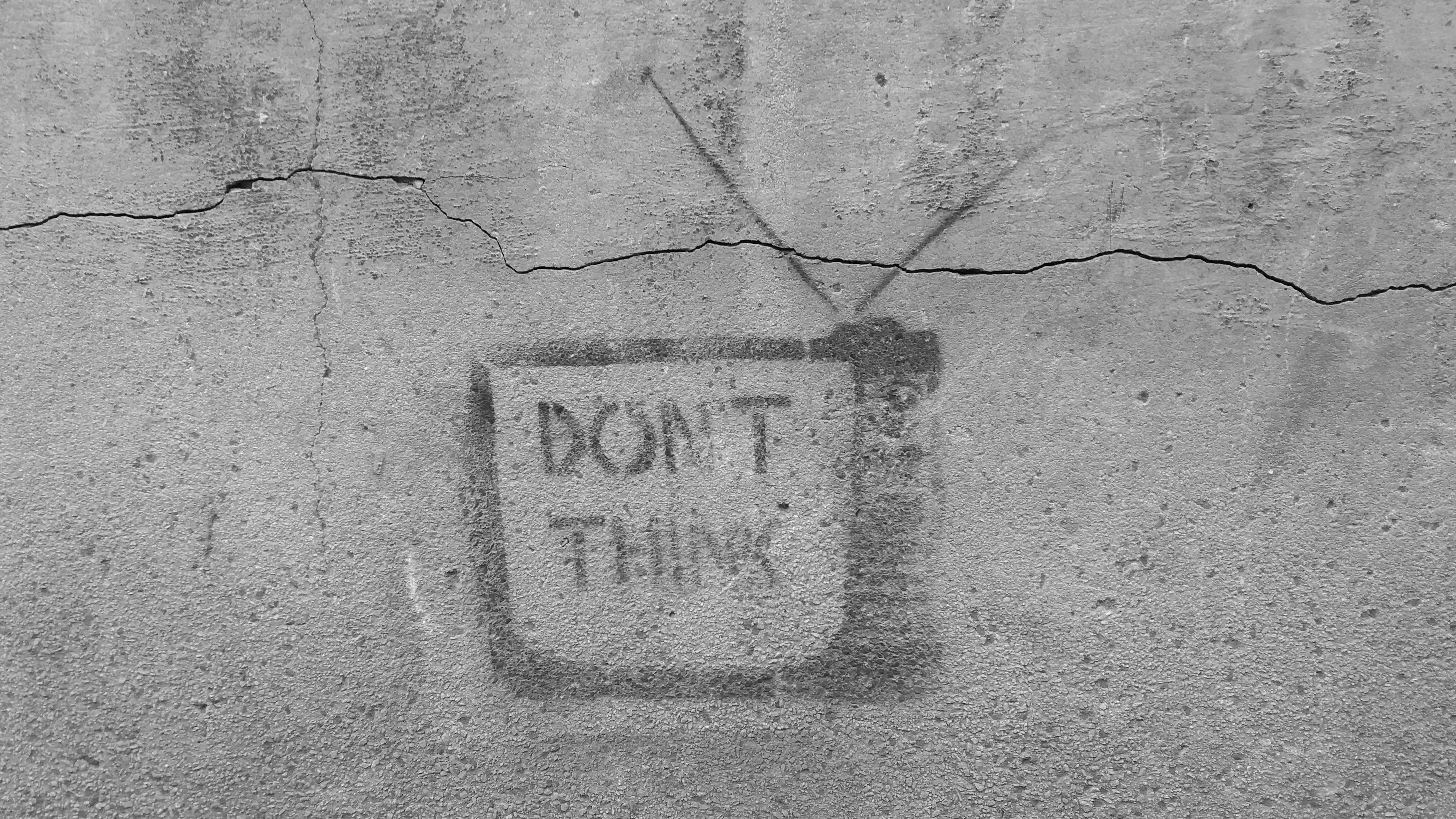 "A faded ""don't think"" graffiti with a television on a gray wall"