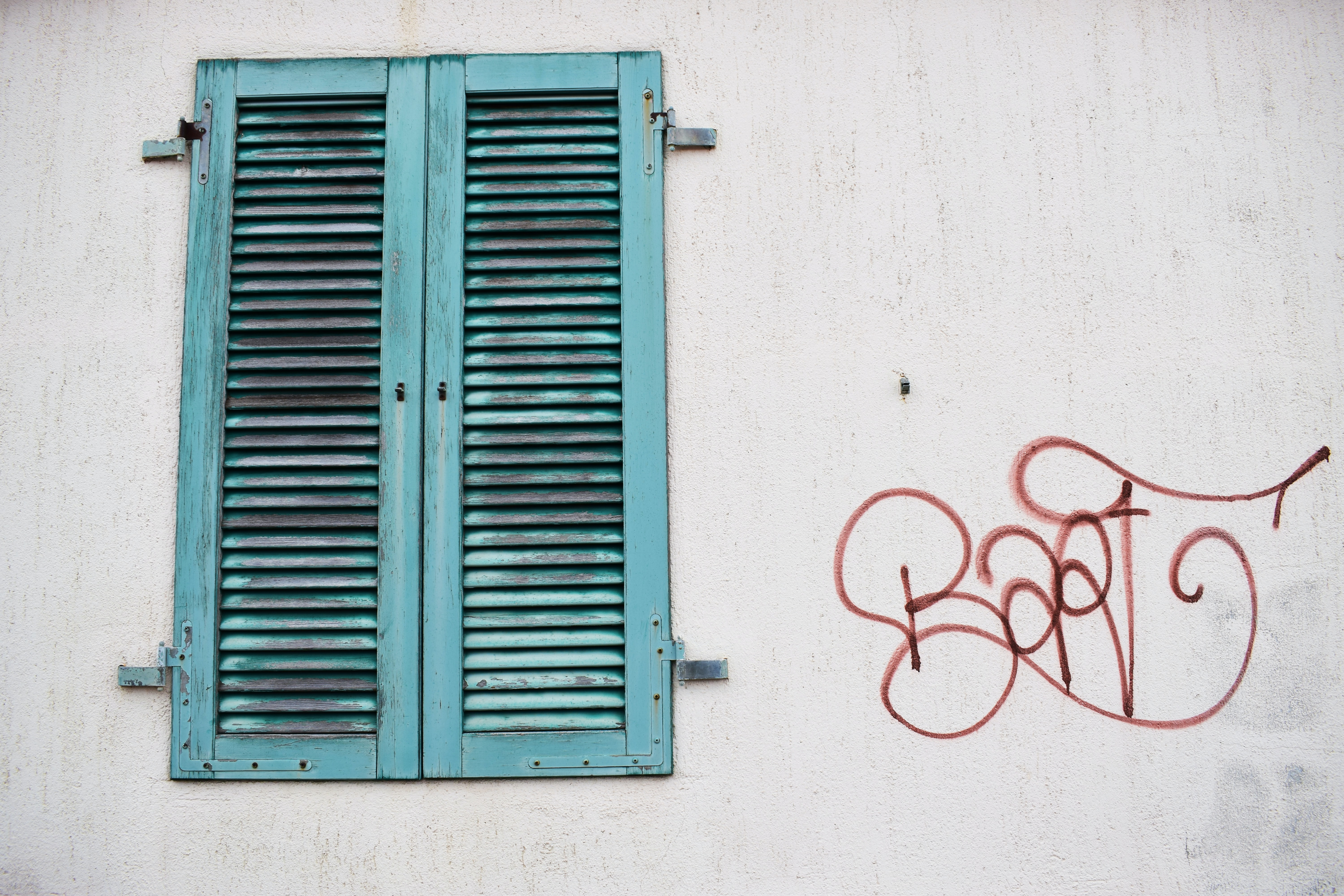 Red graffiti tag on white wall next to worn green window shutter