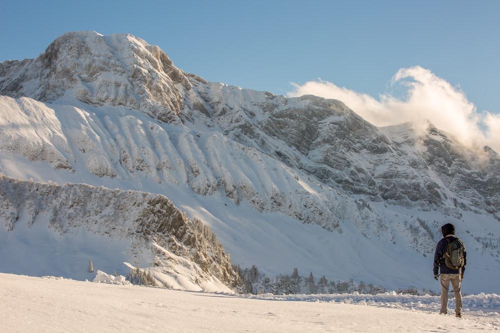 man facing snow covered mountain