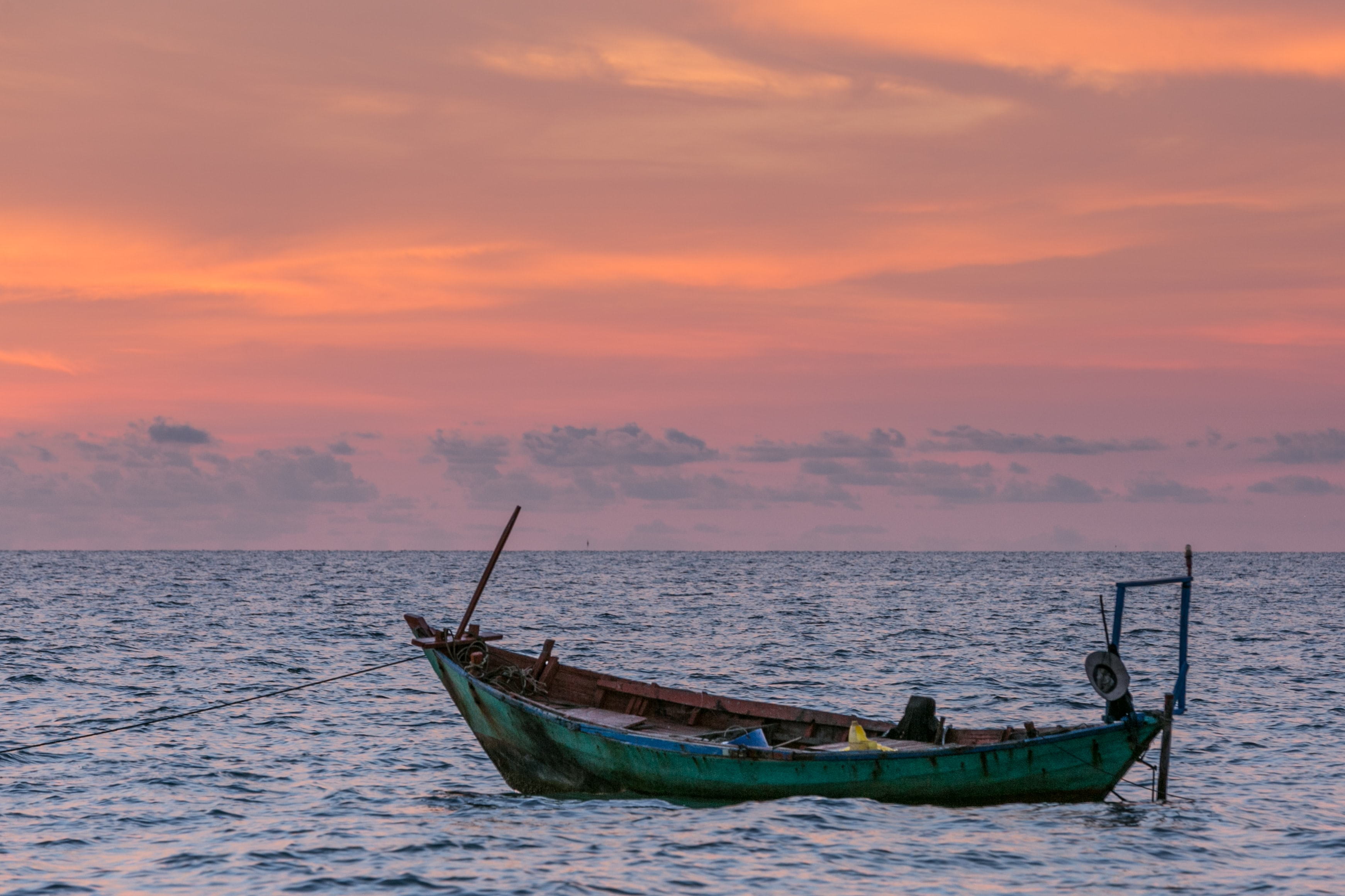 A lone green boat sitting tethered in the ocean, with low clouds at the horizon during sunset