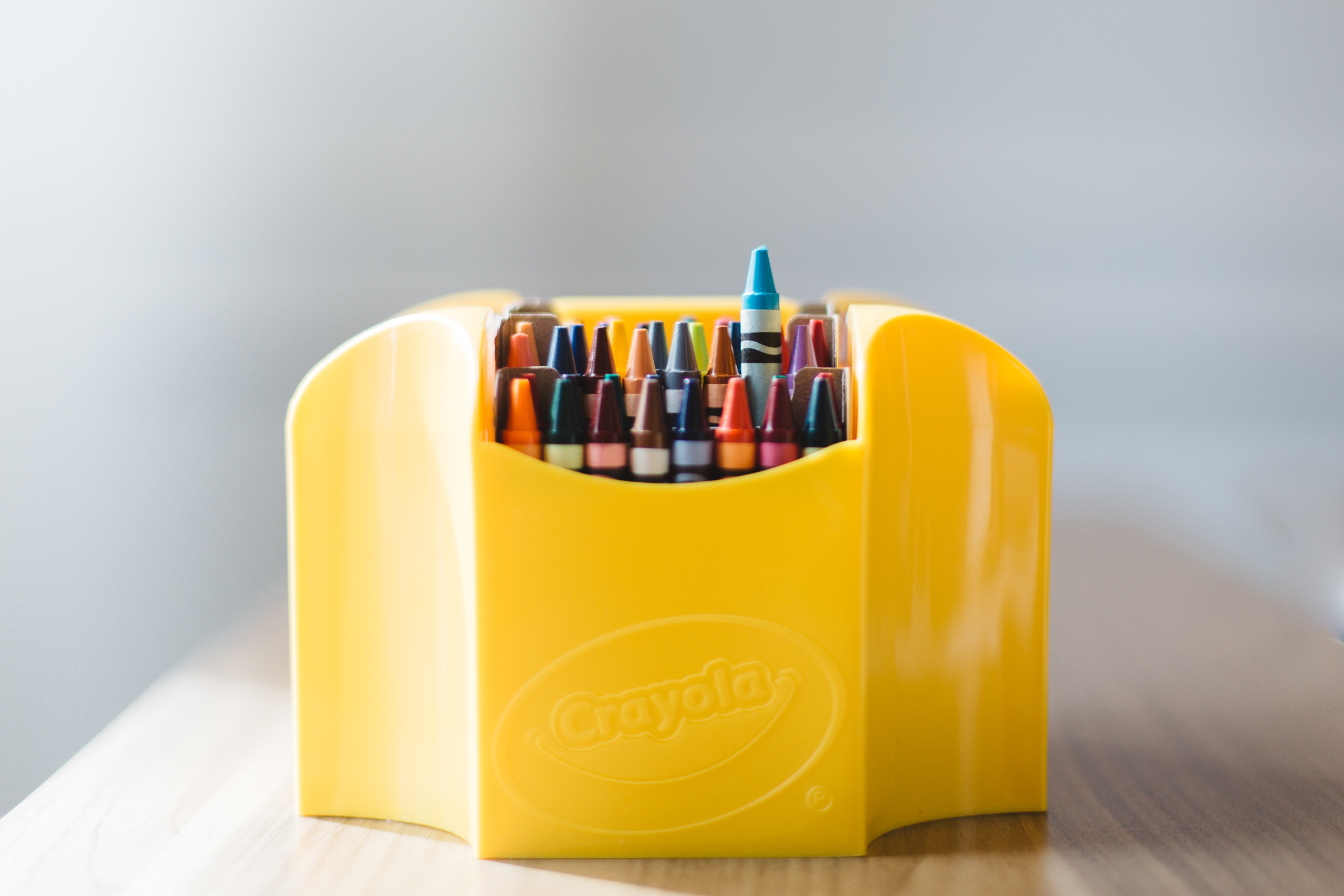 Yellow box of crayons sit on a wooden table
