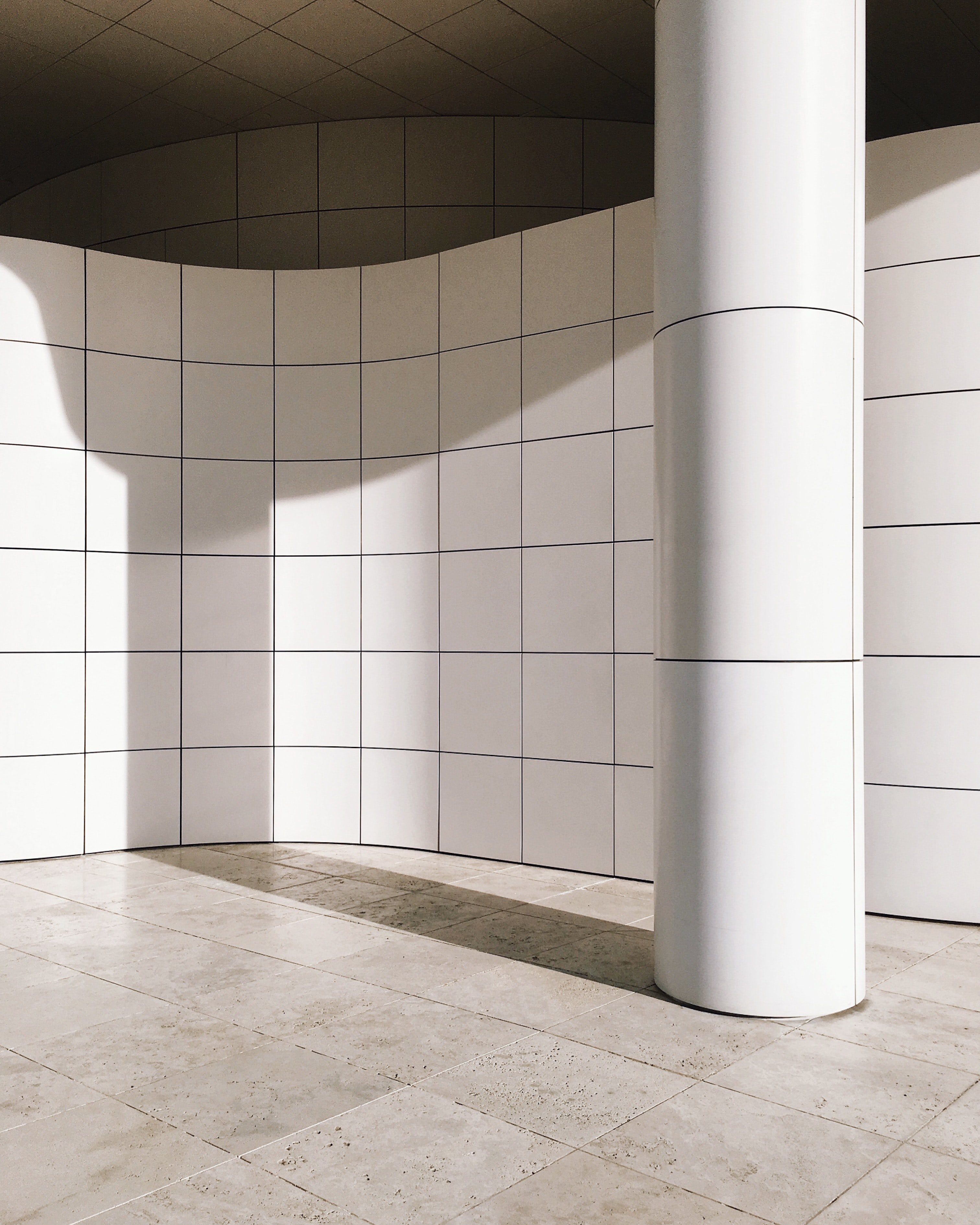 A tiled column casts a shadow onto wall of The Getty museum