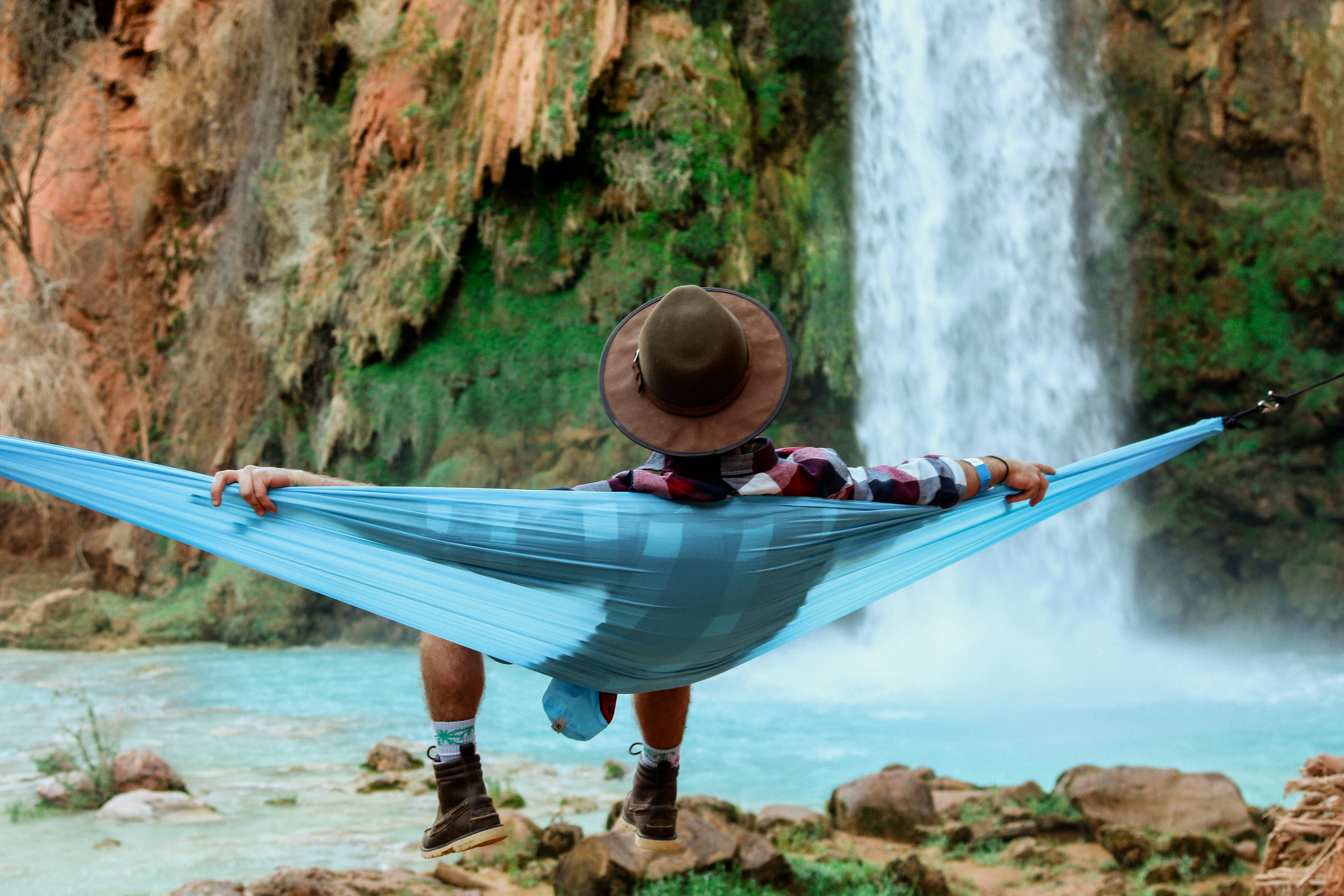 A man wearing a brown hat, plaid shirt, and hiking boots, sitting on a blue hammock in Supai Falls