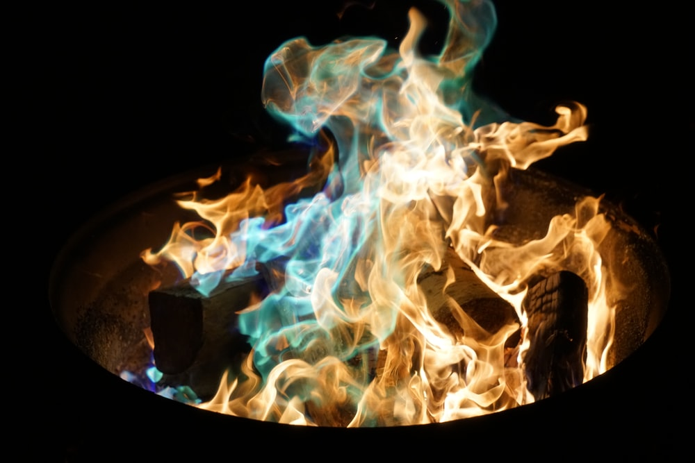 orange and blue flame on pile of wood