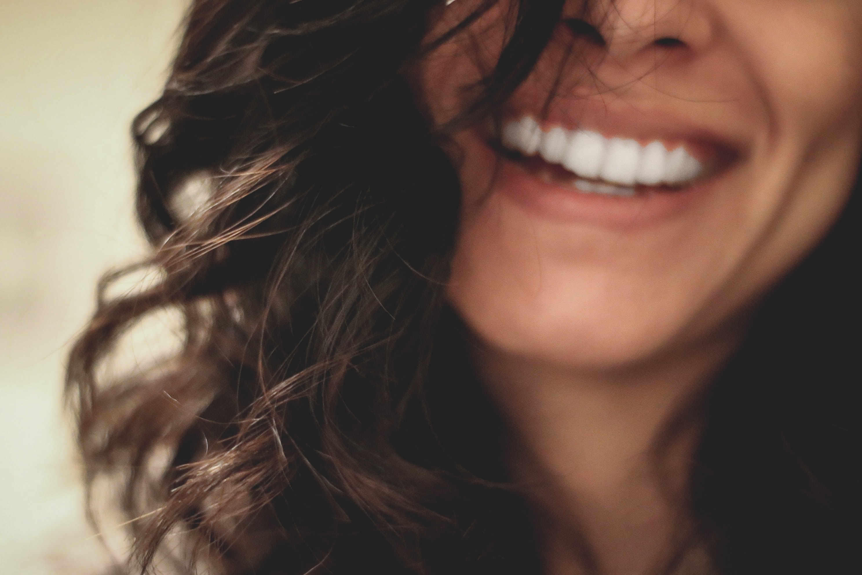 long black haired woman smiling close-up photography