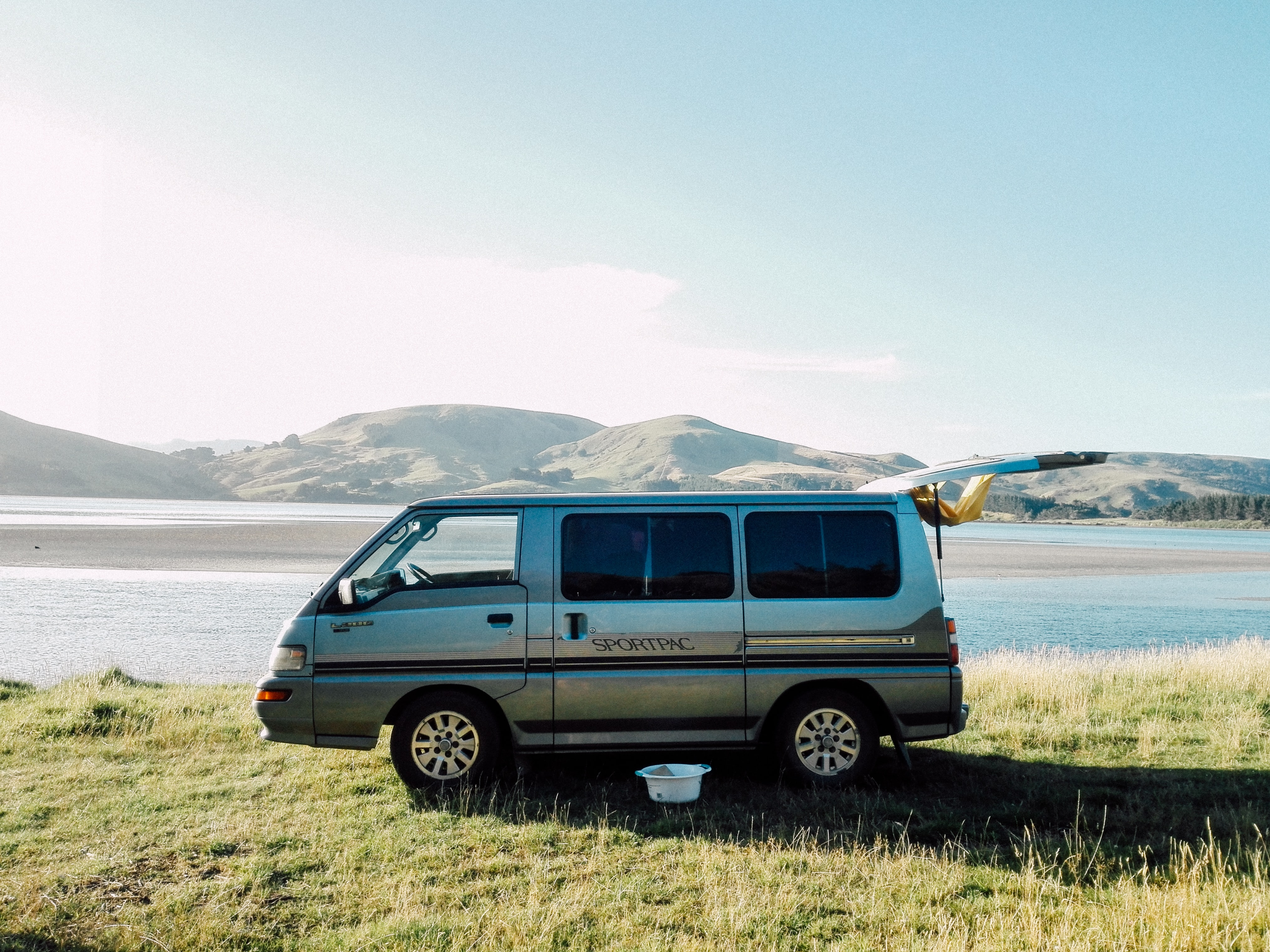 A family van with its back door raised open in the middle of a grassy field beside a lake overlooking distant mountains