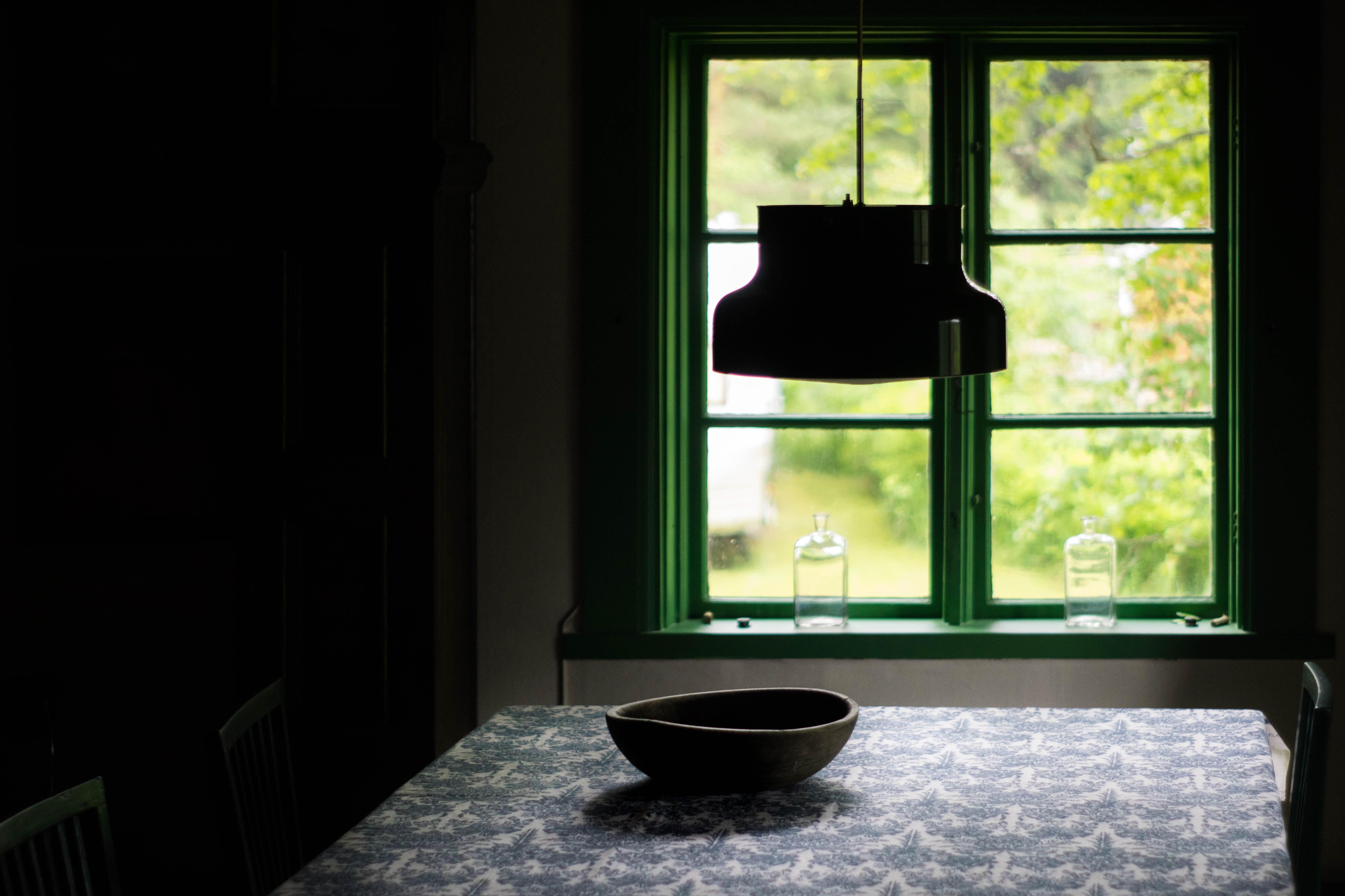 Window with green frame from dark interior with table decor, hanging light and bowl, Borlänge