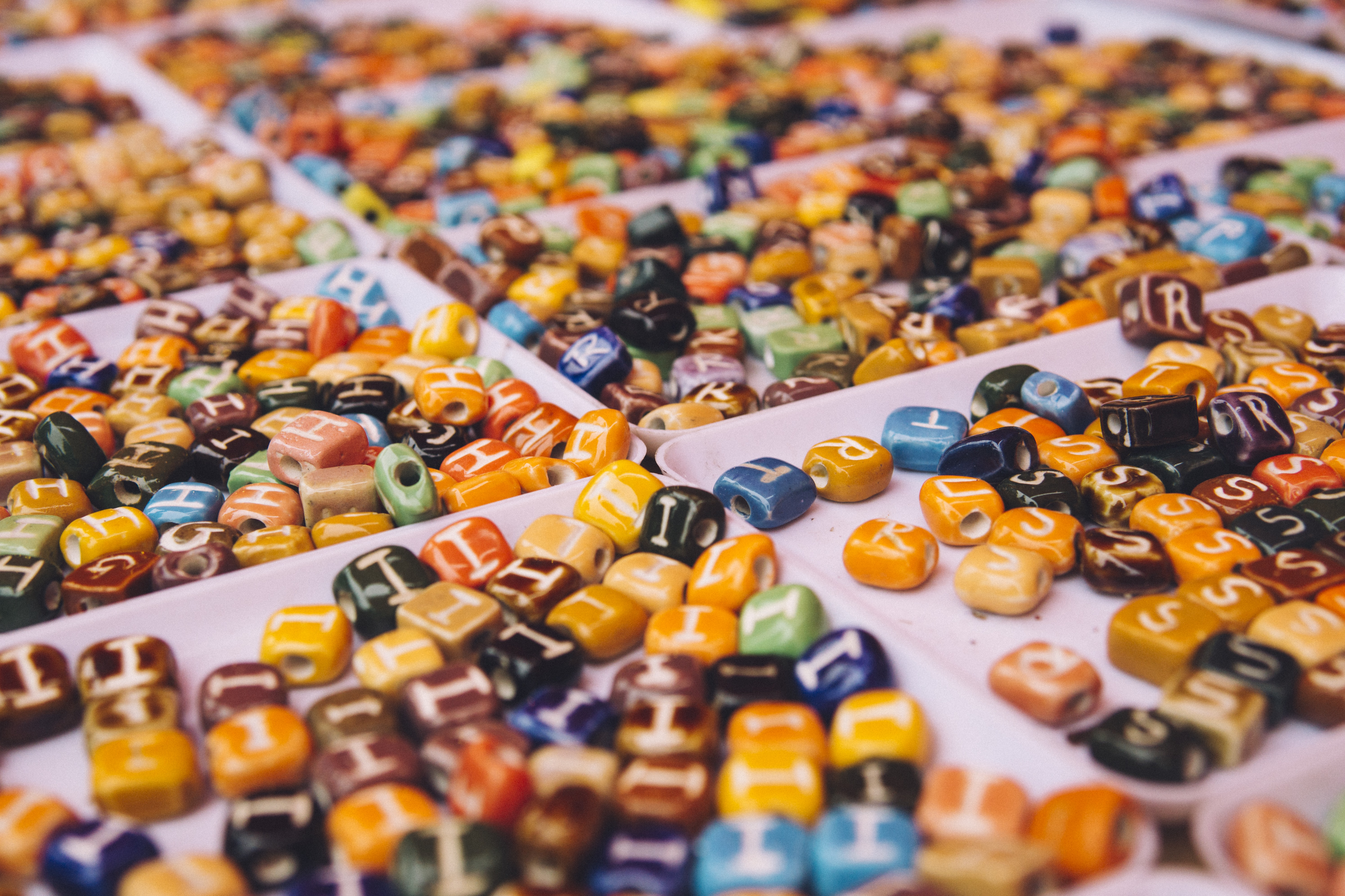 Trays of colorful beads with letters at a craft market
