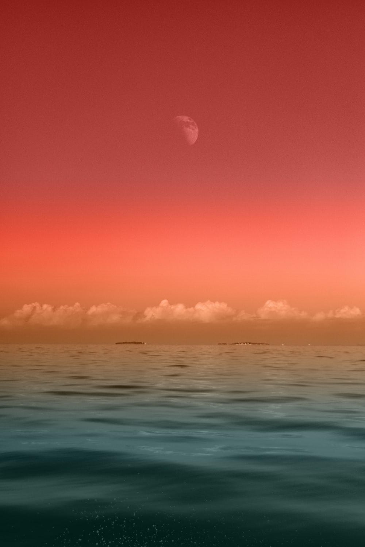 seascape photography of sea under half-moon