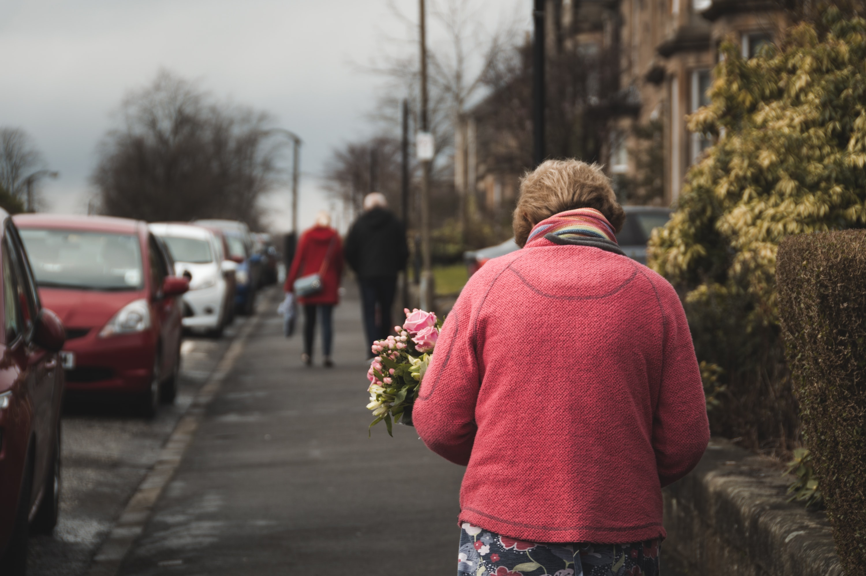 An elderly lady with a bouquet of flowers walking on a suburban sidewalk