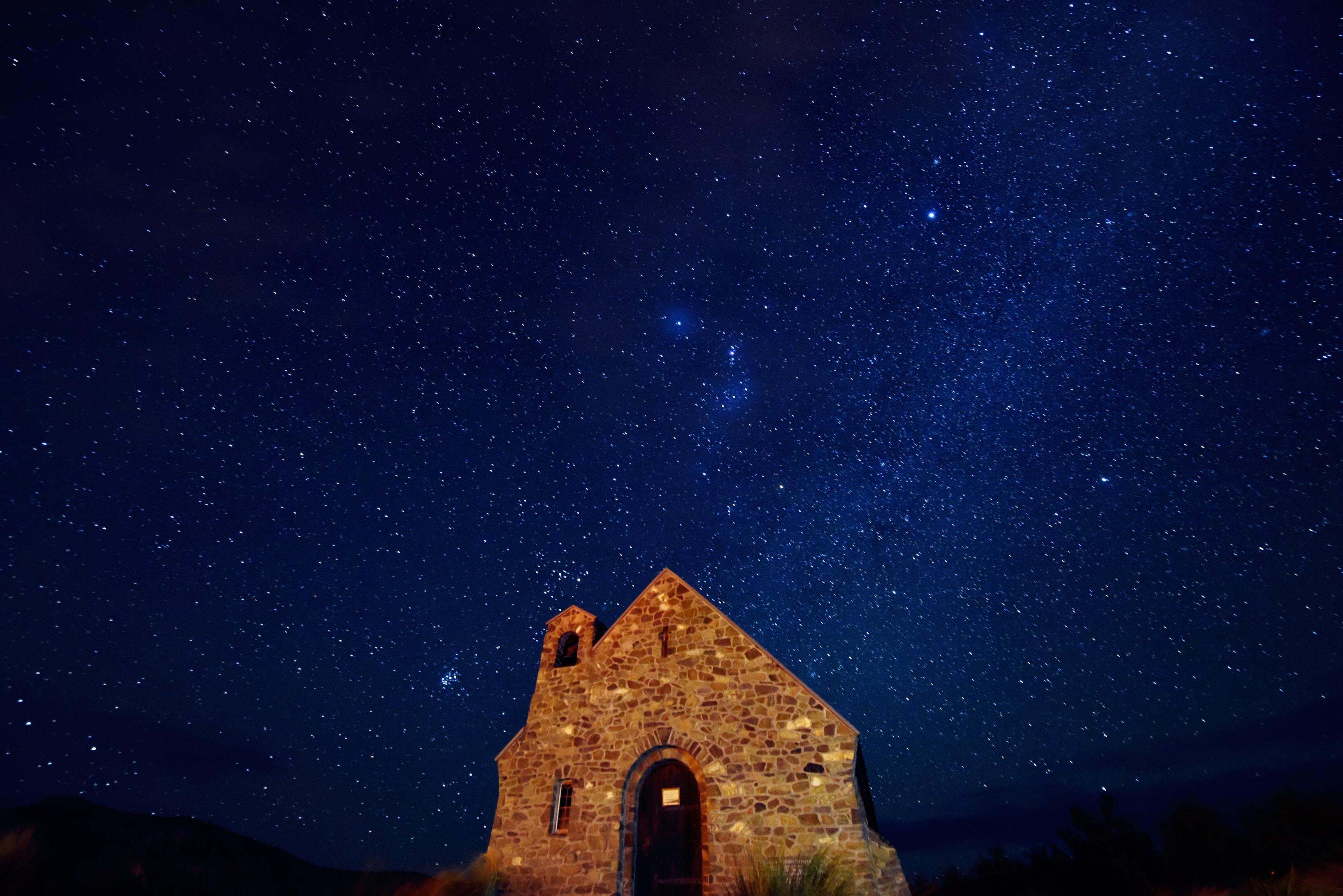 brown brick house under starry night