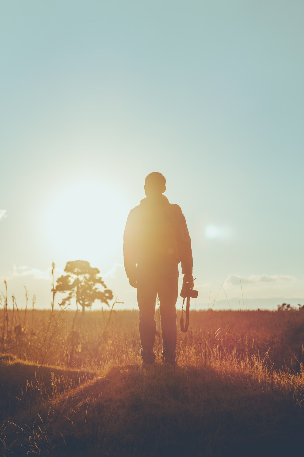 man standing on dried grass holding camera during golden hour