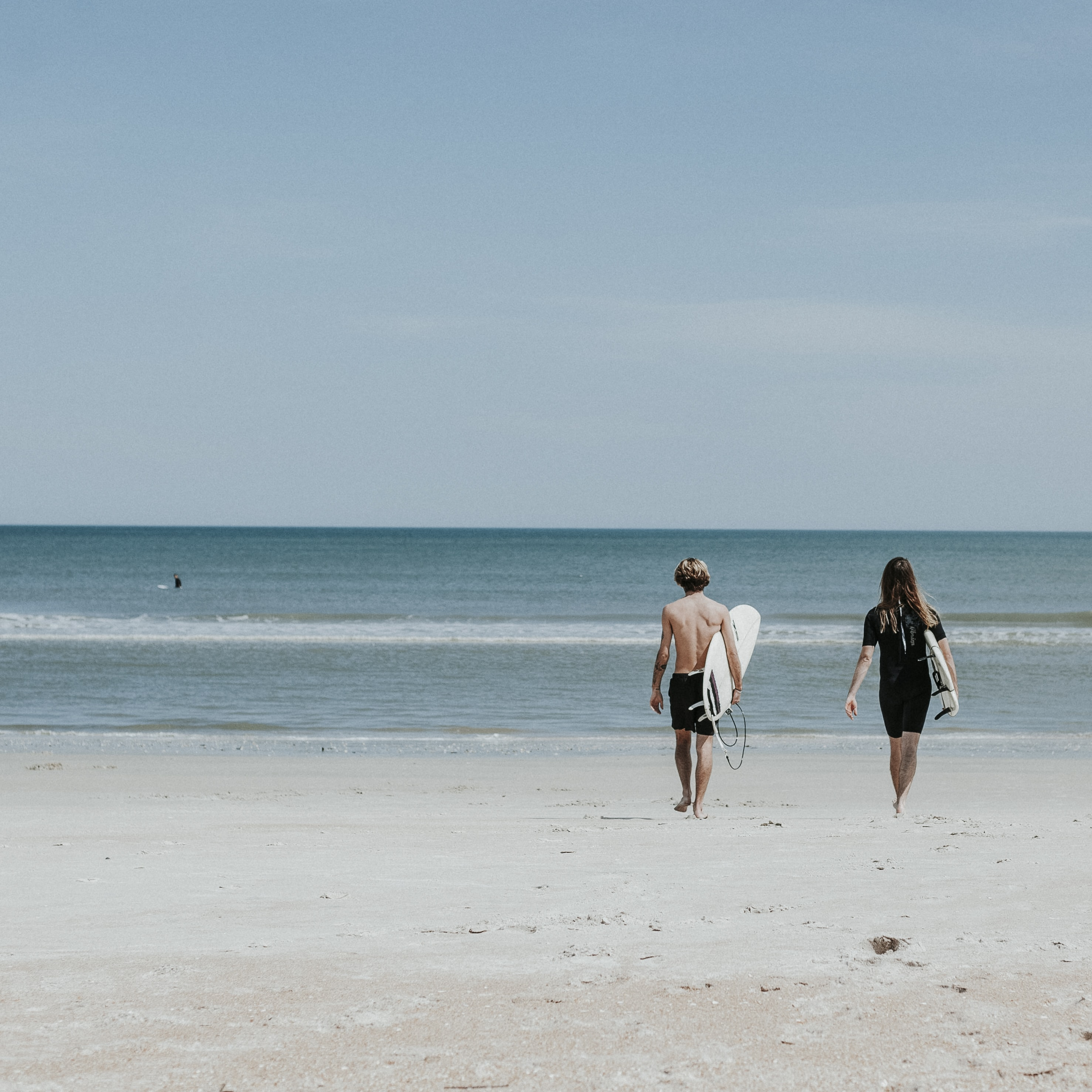 two person walking on coast