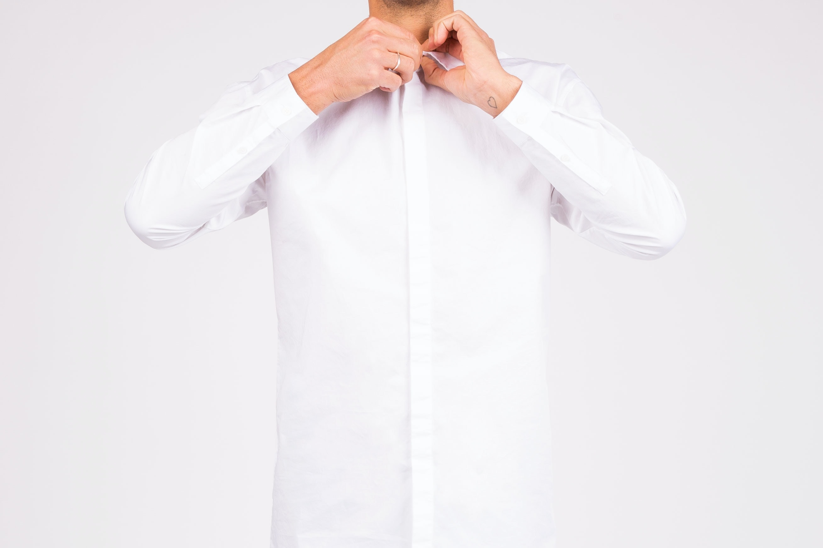 A man buttoning up a white shirt