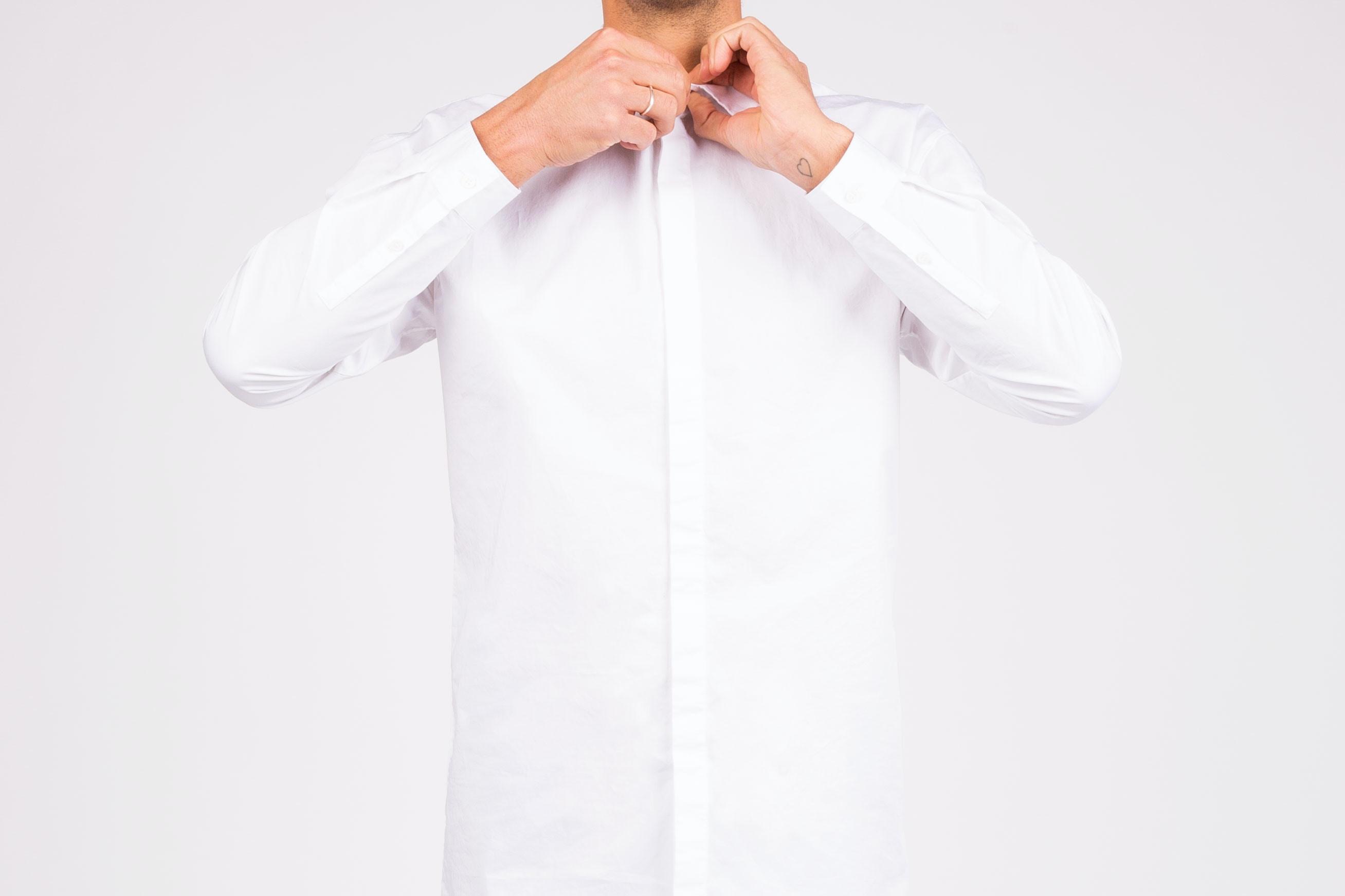 A man buttoning up a white shirt