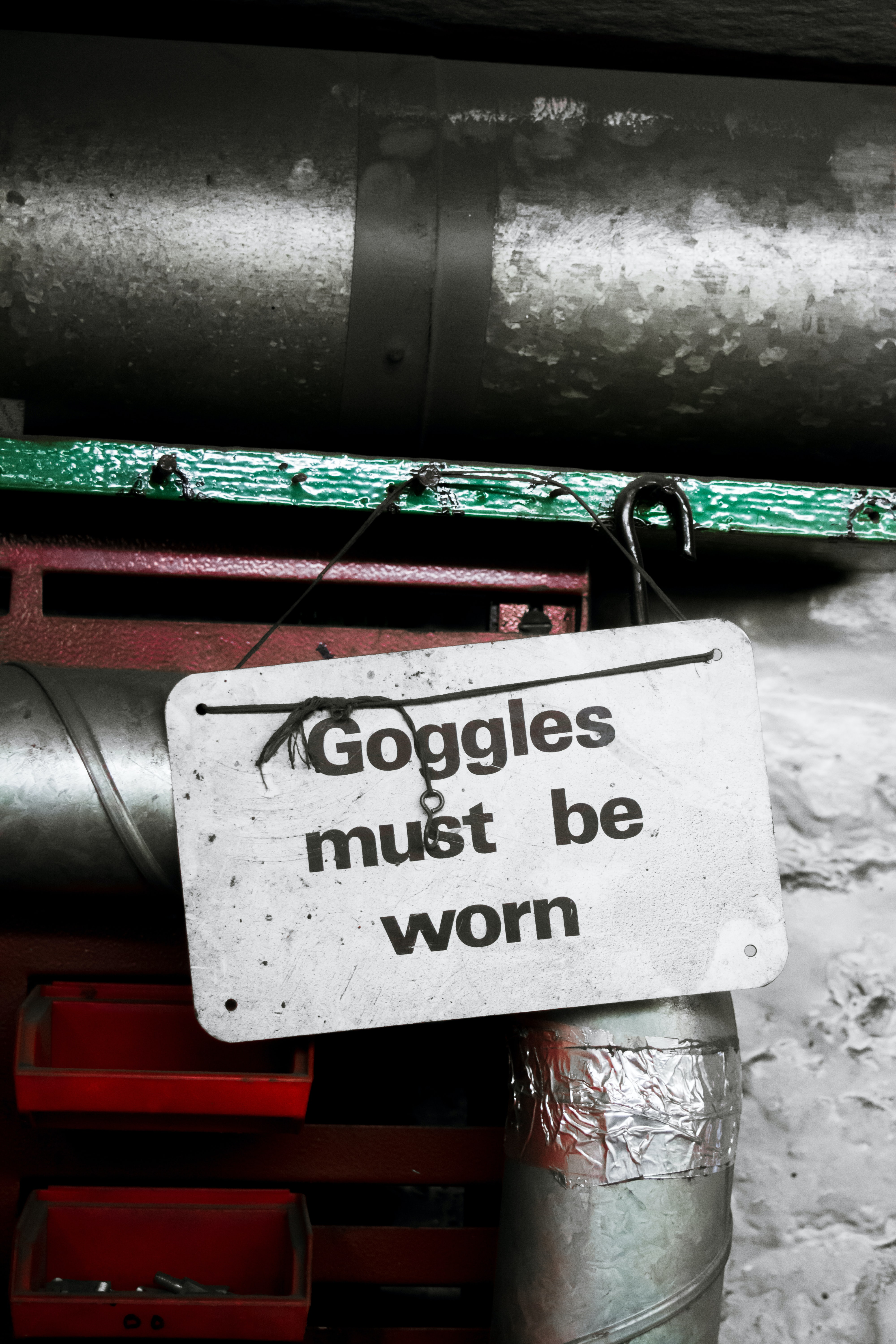 """An industrial room with a safety sign that reads """"goggles must be worn"""""""