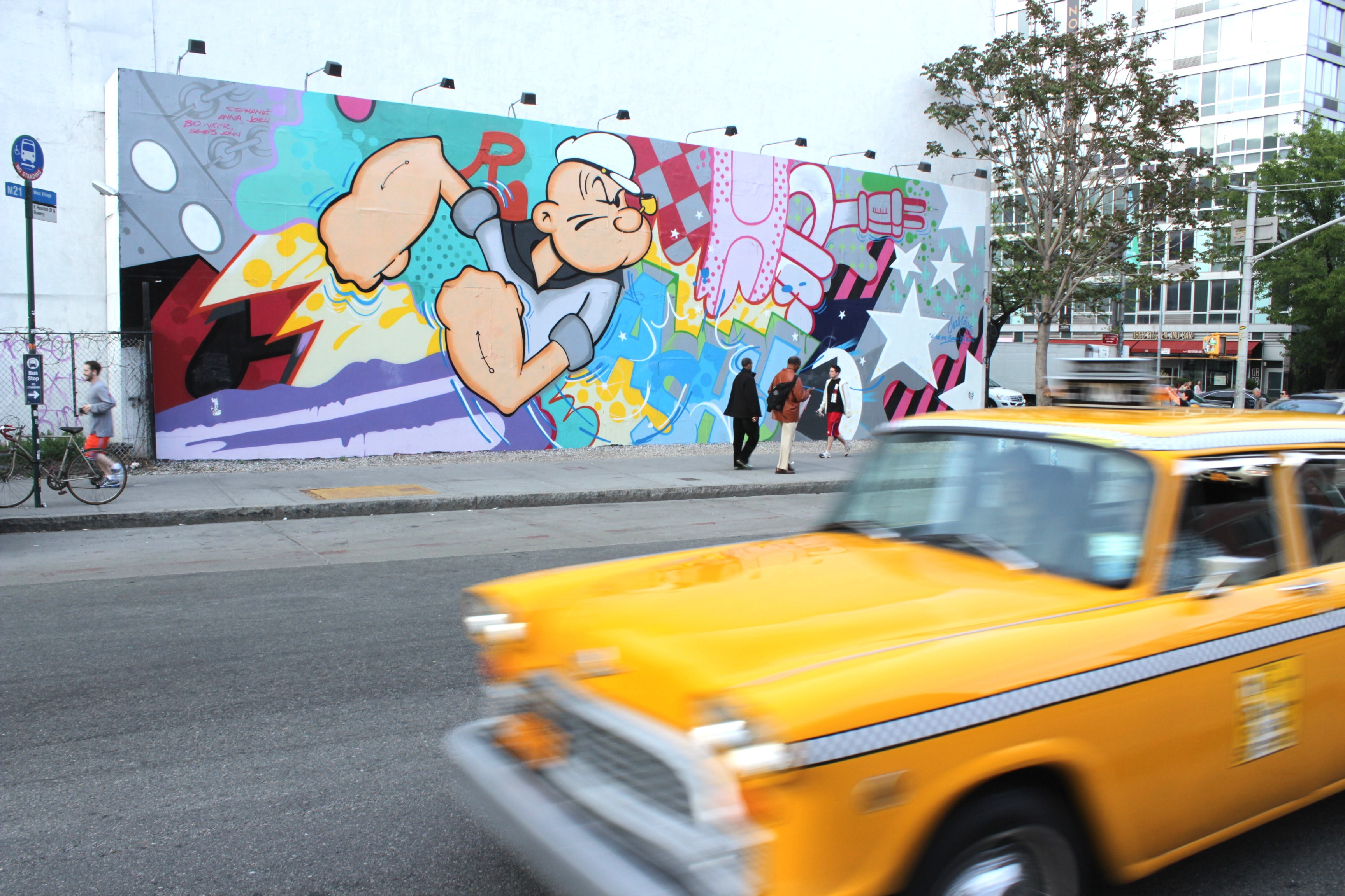 Long shot of colorful popeye graffiti at daytime with yellow taxicab driving past on road