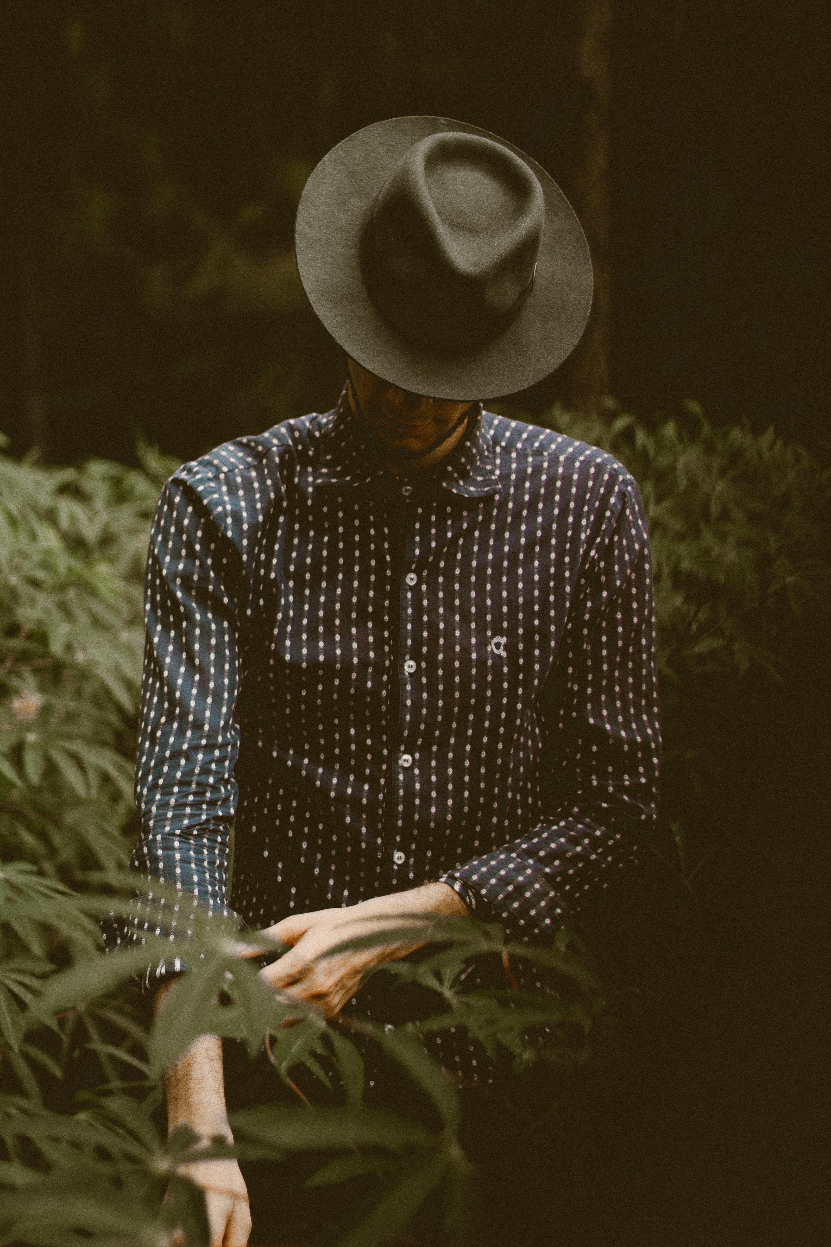 A man standing in the bushes wearing a hat and polka dotted shirt